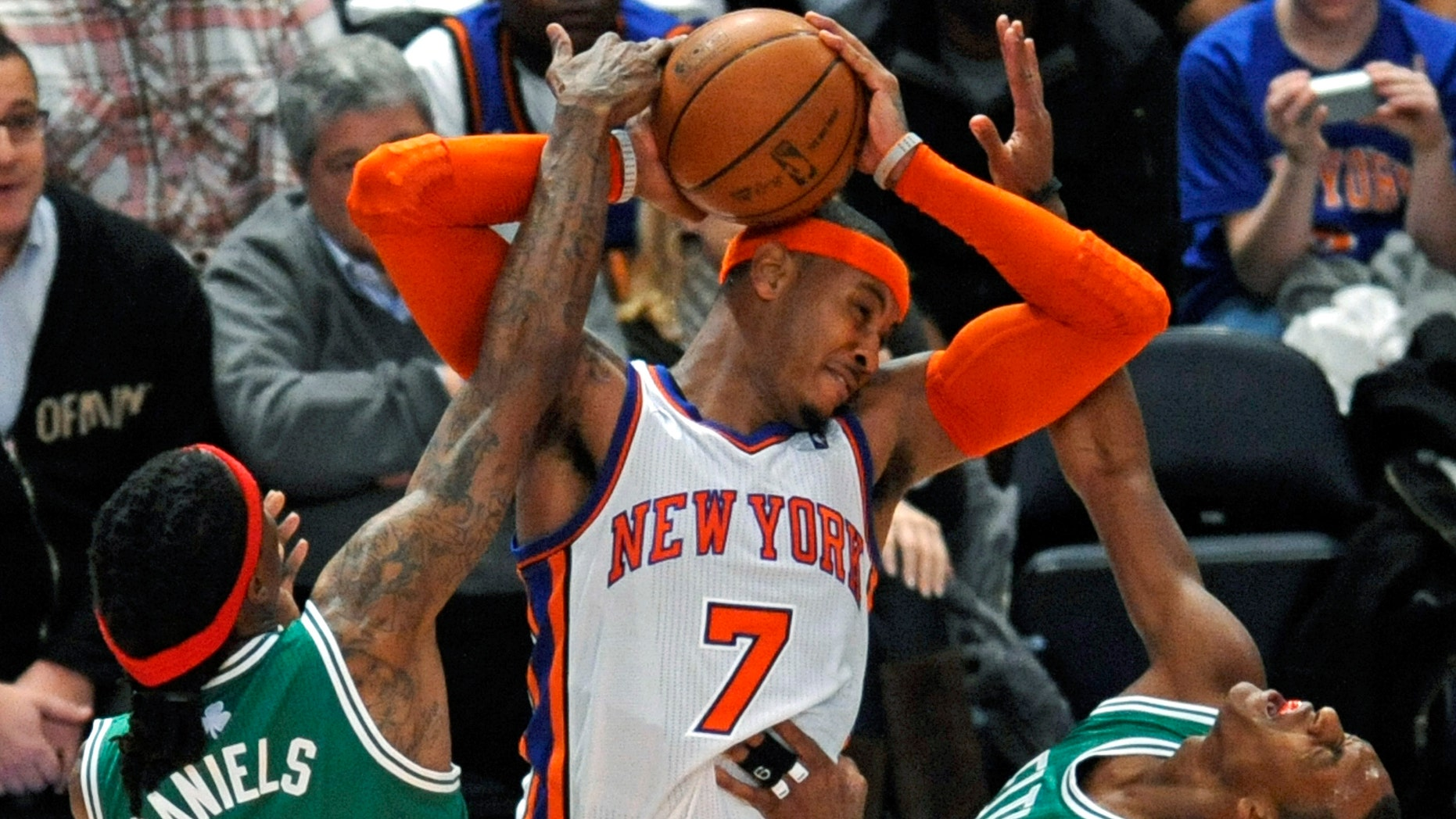 New York Knicks' Carmelo Anthony (7) fouls Boston Celtics' Rajon Rondo, right, with his elbow as he is pressured by Celtics' Marquis Daniels (4) during the third quarter of an NBA basketball game Sunday, Dec. 25, 2011 at Madison Square Garden in New York. Knicks won 106-104. (AP Photo/Bill Kostroun)