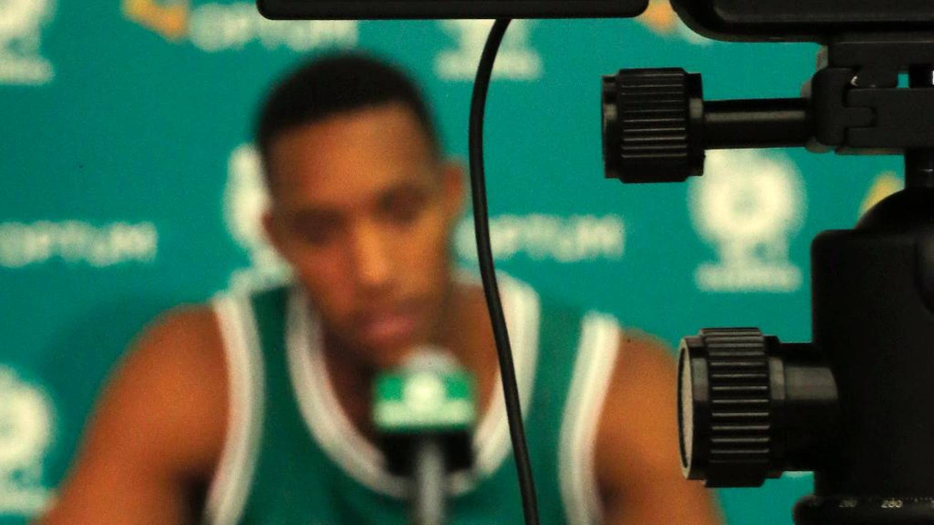 Boston Celtics guard Evan Turner, displayed on the screen of a video camara, speaks to reporters during NBA basketball media day in Waltham, Mass., Monday, Sept. 29, 2014. (AP Photo/Elise Amendola)