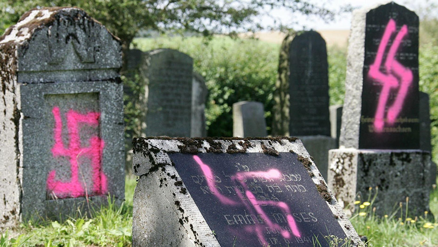 Graves desecrated by vandals with Nazi swastikas and anti-semitic slogans are pictured in the Jewish cemetery of Weyhers, near the city of Ebersburg, Germany