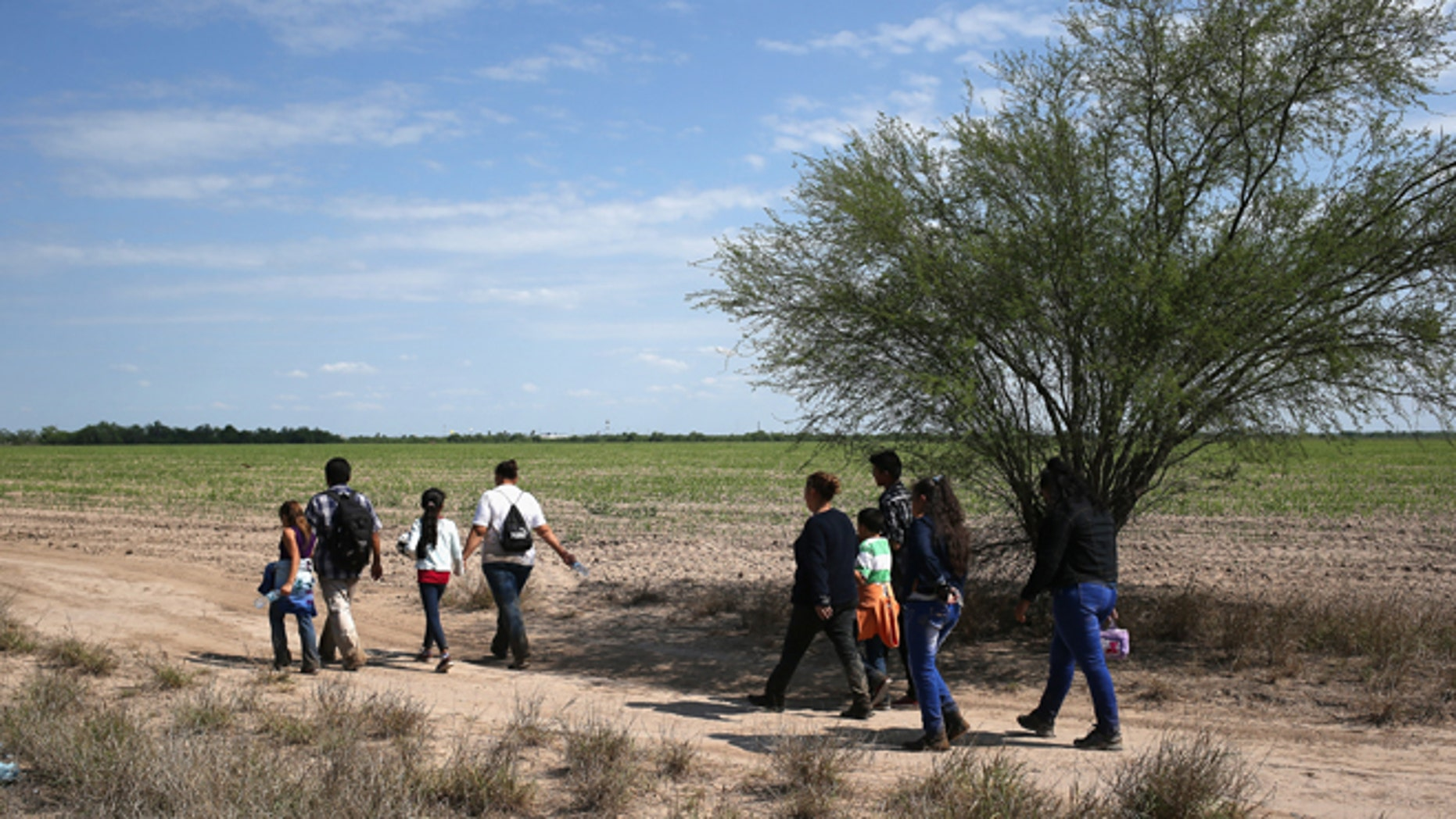 Central American families walk through the countryside after crossing from Mexico on April 14, 2016 in Roma, Texas.