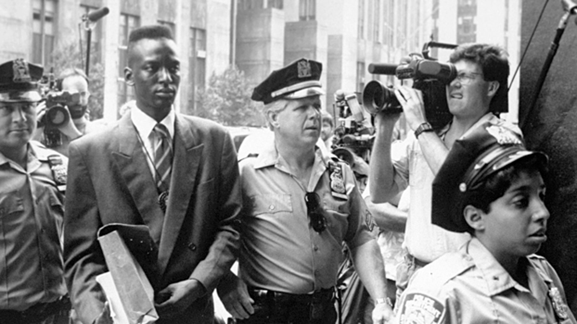 "FILE - This 1990 file photo provided by Sundance Selects shows accused rapist Yusef Salaam, second right, being escorted by police in New York in 1990. Salaam is the subject of the documentary, ""The Central Park Five,"" about the 1989 case of five black and Latino teenagers who were convicted of raping a white woman in Central Park. A city official said Friday, June 20, 2014 that New York City has agreed to a $40 million settlement in a civil rights lawsuit filed against police and prosecutors by Salaam and four co-defendants exonerated in the notorious case of a jogger attacked in Central Park in 1989. (AP Photo/Sundance Selects, NY Daily News, File)"