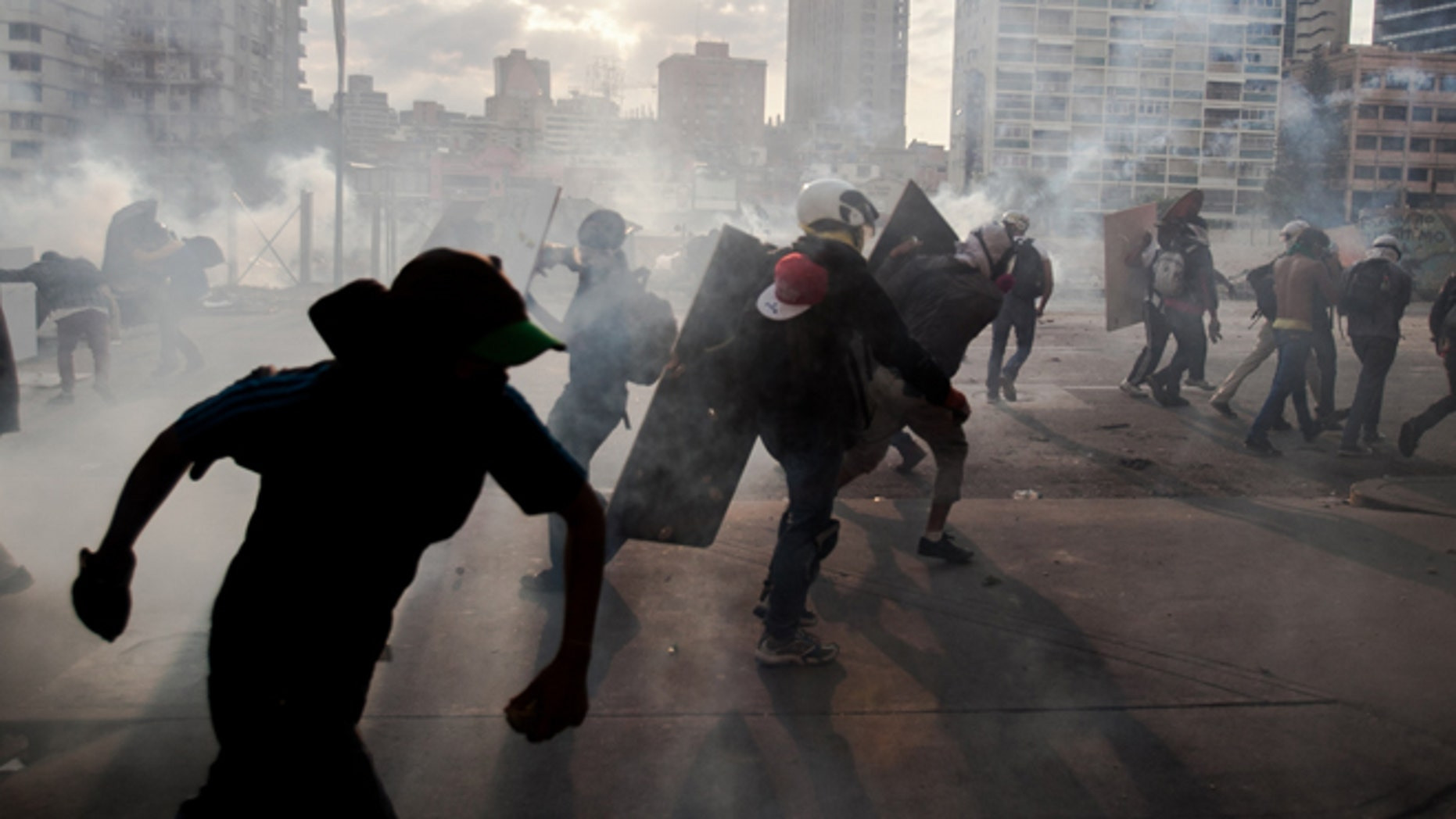 Demonstrators take cover from teargas fired by the police during clashes in an anti-government protest in Caracas, Venezuela, Monday, March 10, 2014. The Venezuelan government and opposition appear to have reached a stalemate, in which street protests continue almost daily while the opposition sits out a peace process it calls farcical. (AP Photo/Alejandro Cegarra)