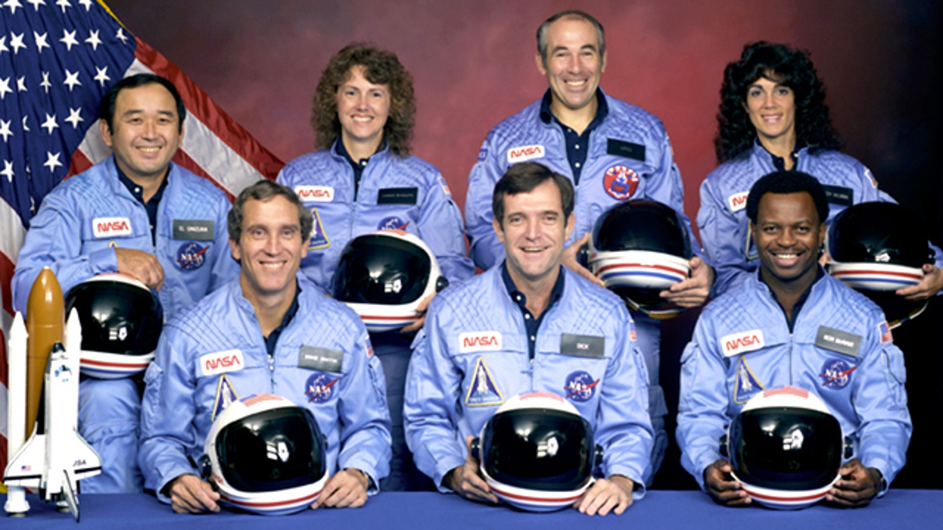 An official portrait shows the STS-51L crewmembers. Back row (L to R): Mission Specialist, Ellison S. Onizuka, Teacher in Space Participant Sharon Christa McAuliffe, Payload Specialist, Greg Jarvis and Mission Specialist, Judy Resnik. Front row (L to R): Pilot Mike Smith, Commander, Dick Scobee and Mission Specialist, Ron McNair.