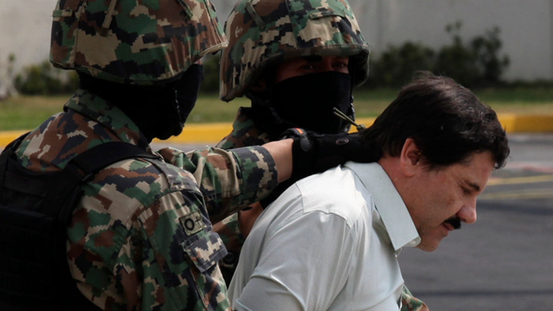 """Joaquin """"El Chapo"""" Guzman is escorted to a helicopter by Mexican navy marines in Mexico City, on Feb. 22, 2014."""