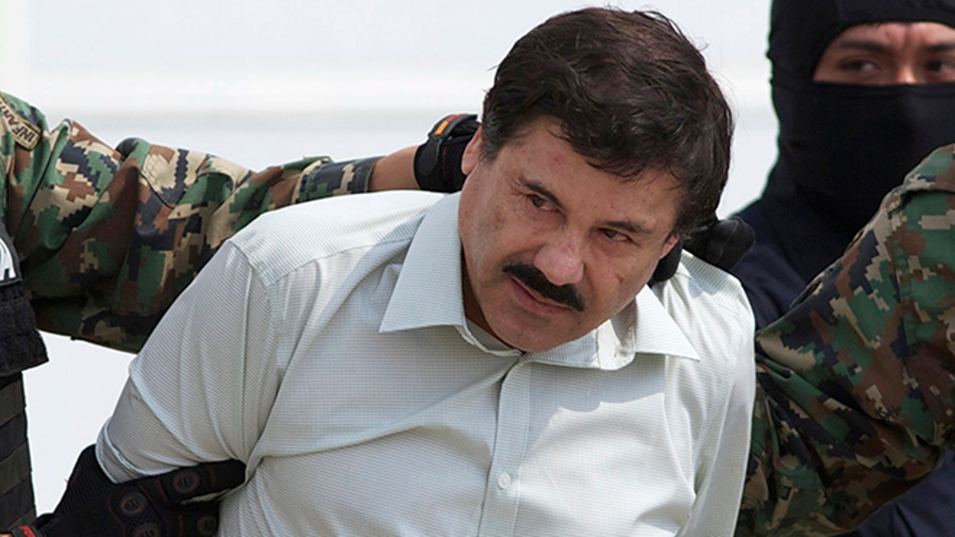 """FILE - In this Feb. 22, 2014, file photo, Joaquin """"El Chapo"""" Guzman, head of Mexicoâs Sinaloa Cartel, is escorted to a helicopter in Mexico City, following his capture overnight in the beach resort town of Mazatlan. Mexicoâs security commission said in a statement late Saturday, July 11, 2015, the top drug lord Joaquin âEl Chapoâ Guzman has escaped from a maximum security prison, the second time he has fled after being captured. (AP Photo/Eduardo Verdugo, File)"""