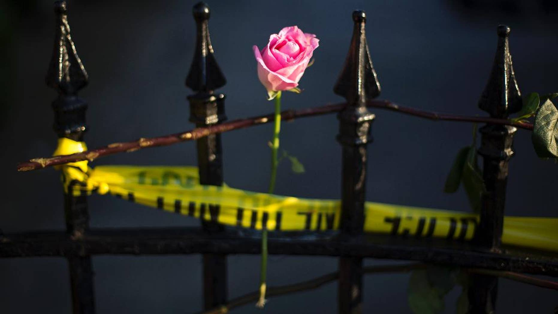 A rose is affixed to a fence along a sidewalk memorial in memory of the shooting victims in front of Emanuel AME Church Saturday, June 20, 2015, in Charleston, S.C. The current brick Gothic revival edifice, completed in 1891 to replace an earlier building heavily damaged in an earthquake, was a mandatory stop for the likes of Booker T. Washington and the Rev. Martin Luther King Jr. Still, Emanuel was not just a church for the black community.(AP Photo/David Goldman)