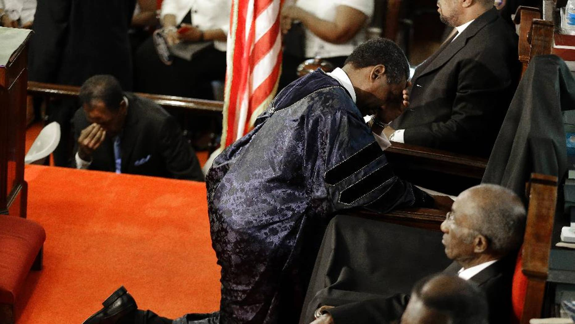 FILE - In this June 21, 2015, file photo, Rev. Norvel Goff prays at the empty seat of the Rev. Clementa Pinckney at the Emanuel A.M.E. Church four days after a mass shooting that claimed the lives of Pinckney and eight others in Charleston, S.C. Some family members of those killed in the church shooting have said they forgive the man who's been charged. But others in the African-American community say offering forgiveness so quickly may not be the best idea. (AP Photo/David Goldman, Pool, File)