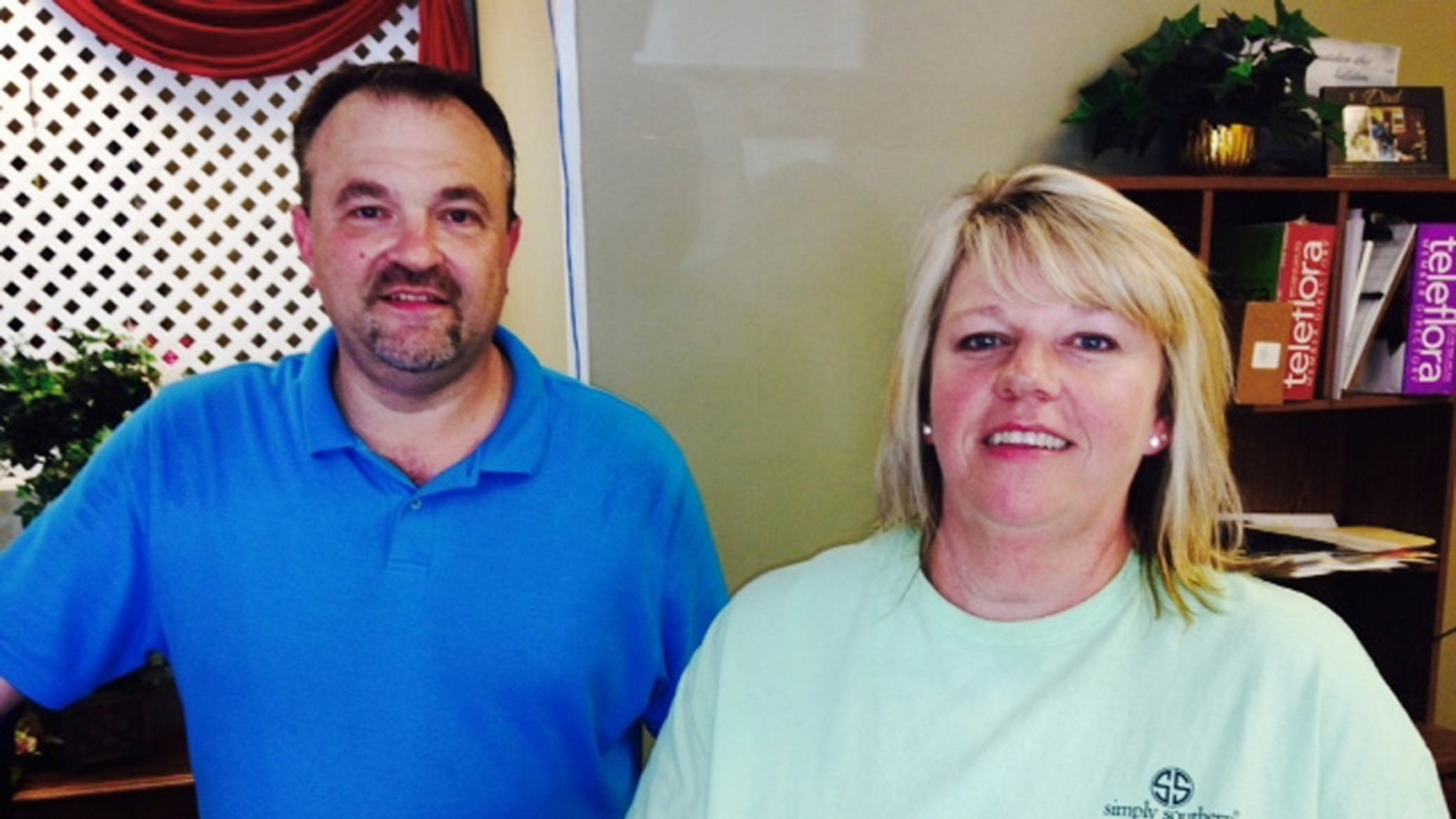 Todd Frady, left, and Debbie Dills of Frady's Florist in Kings Mountain, N.C., pose for a photo Thursday, June 18, 2015, after Dills called in the tip that ultimately led to the arrest of Dylann Storm Roof, the white man who police say killed people at a prayer meeting Wednesday at a black church in Charleston, S.C. Dills says she called Frady when she saw Roof driving, and Frady called a police officer he knew. (AP Photo/Steve Reed)