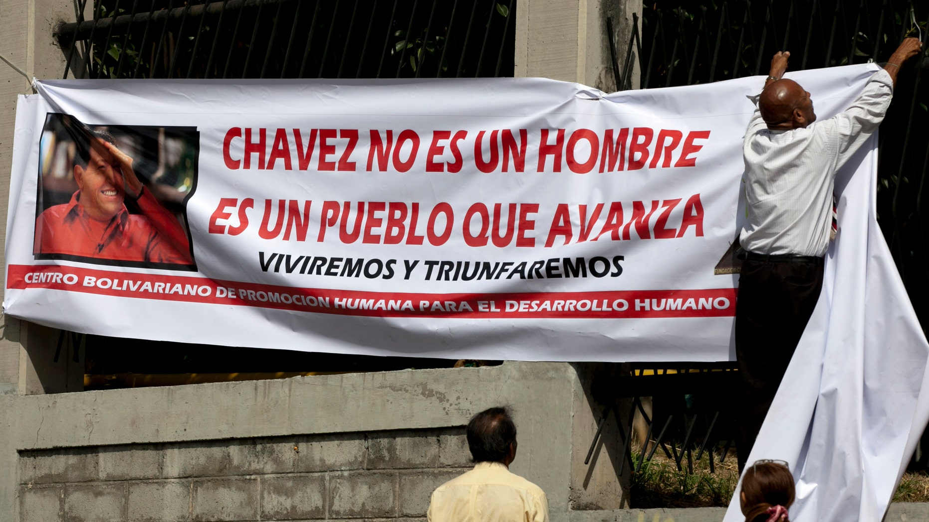 A man hangs a banner showing a picture of Venezuela's President Hugo Chavez outside the Military Hospital, where Chavez is allegedly receiving treatment, in Caracas, Venezuela, Thursday, Feb. 21, 2013. (AP Photo/Ariana Cubillos)