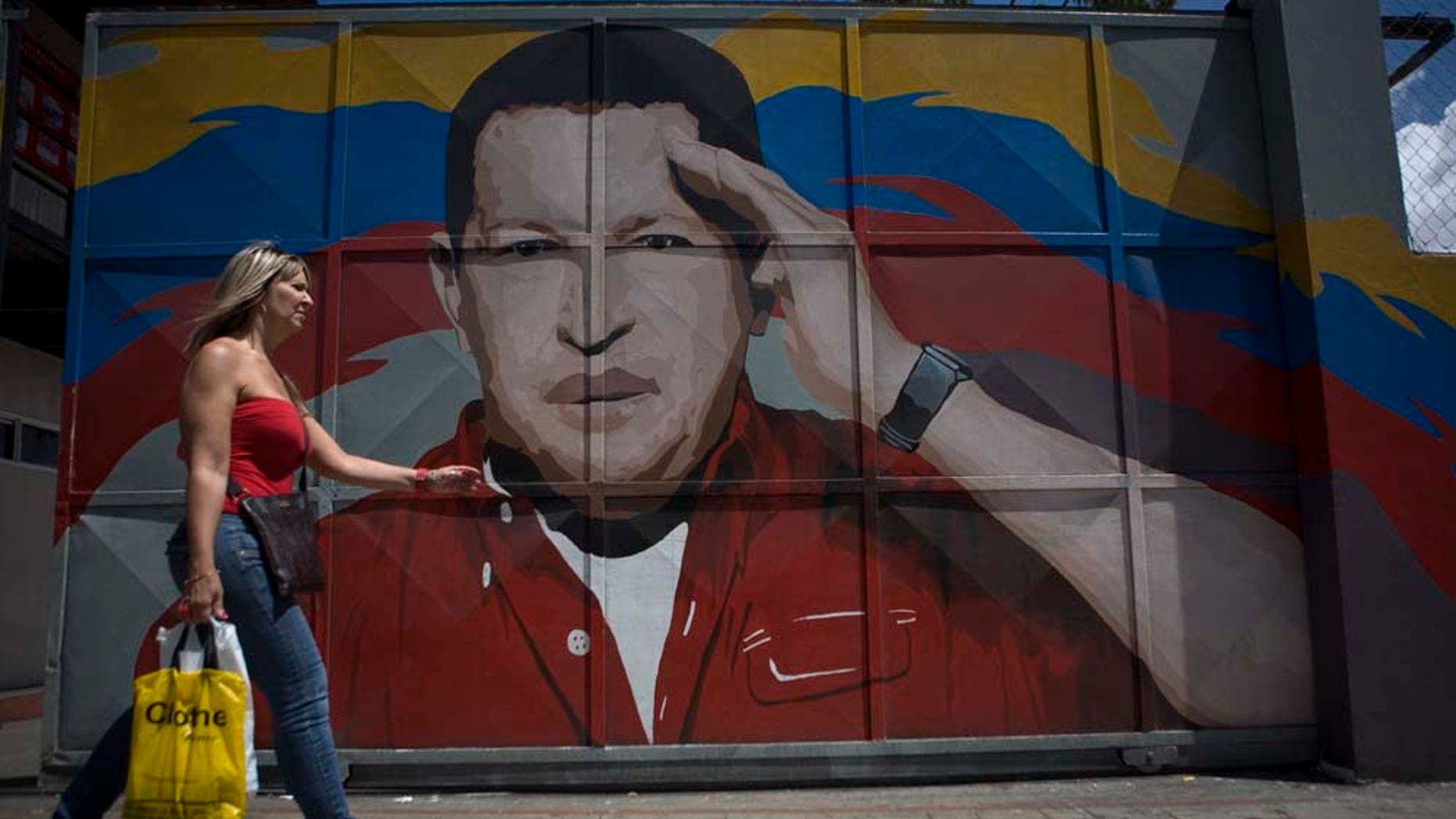 A woman walks by a gate with a painting depicting Venezuela's President Hugo Chavez in Caracas, Venezuela, Wednesday, June 29, 2011. Chavez underwent surgery in Cuba two weeks ago and has been unusually quiet since then. Allies of Chavez have insisted the leader is firmly in control of the country and improving from his operation for a pelvic abscess.(AP Photo/Ariana Cubillos)