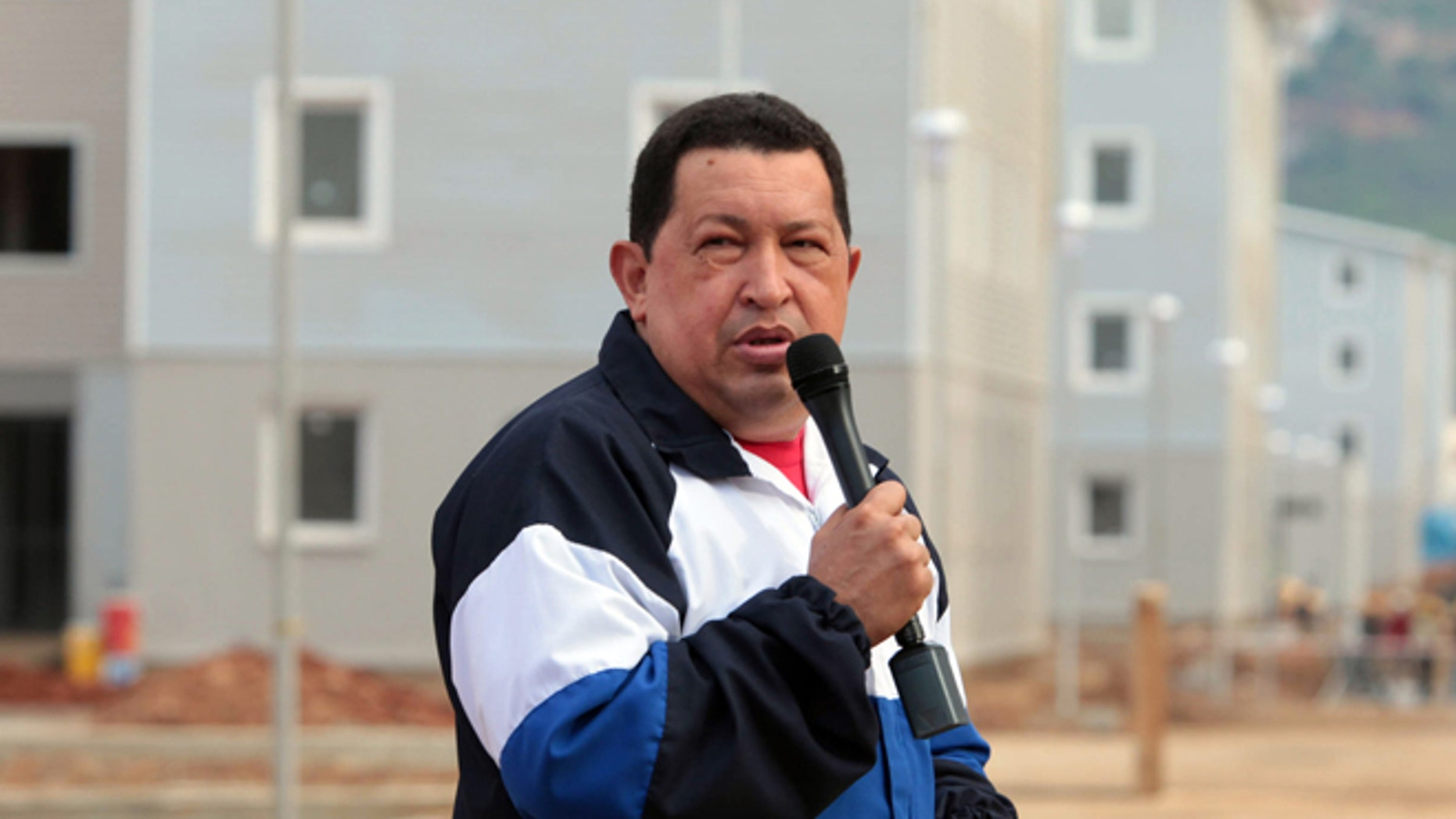 In this photo released by Miraflores Press Office, Venezuela's President Hugo Chavez speaks during a visit to a housing complex at Catia la Mar, Venezuela, Thursday, Aug. 9, 2012. Chavez says Venezuelan security forces have arrested a U.S. citizen and suspect he is a mercenary who could be involved in an alleged plot to destabilize the country if the opposition's candidate loses the upcoming presidential election. (AP Photo/Miraflores Press Office)