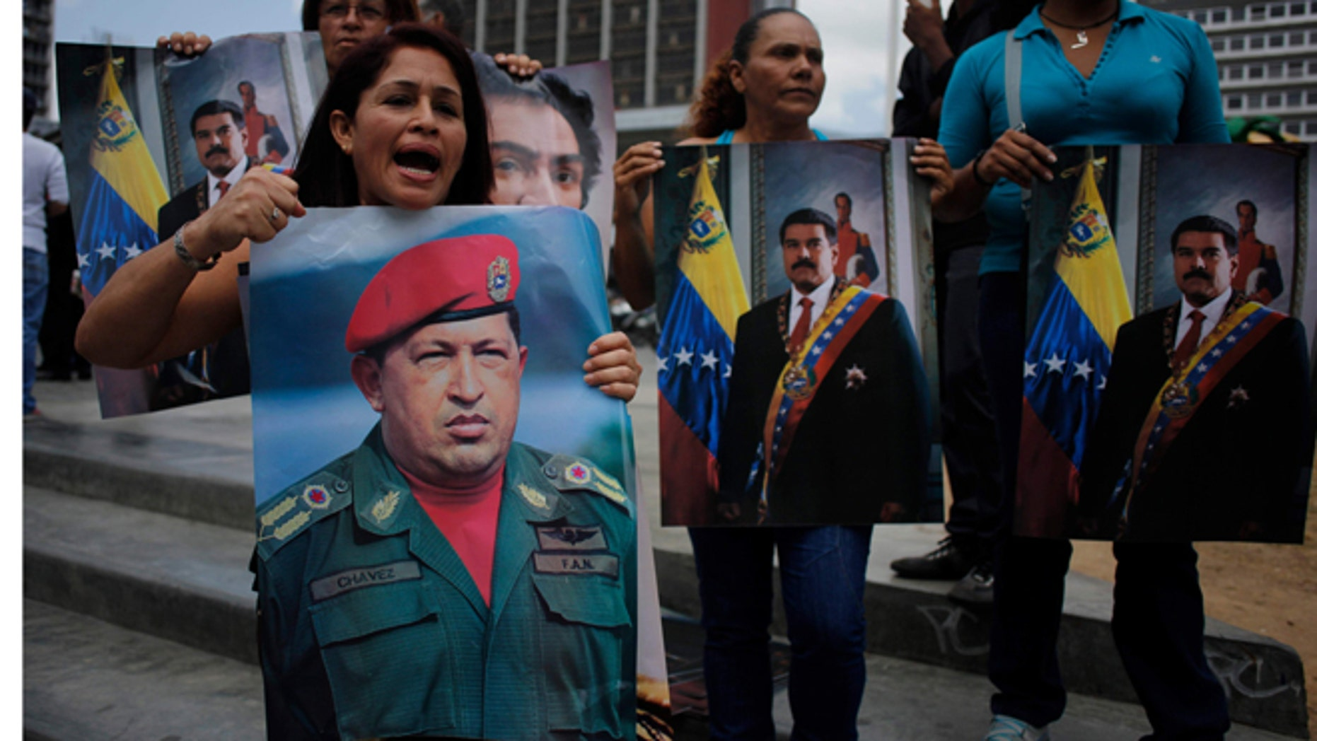 Supporters of Venezuela's President Nicolas Maduro, hold posters of him and of late Venezuelan President Hugo Chavez during a demonstration outside the Palace of justice in Caracas, Venezuela, Wednesday, Feb. 19, 2014. Following a dramatic surrender and a night in jail, Venezuelan opposition leader Leopoldo Lopez was due in court Wednesday to learn what charges he may face for allegedly provoking violence during protests against the socialist government in the divided nation. (AP Photo/Rodrigo Abd)