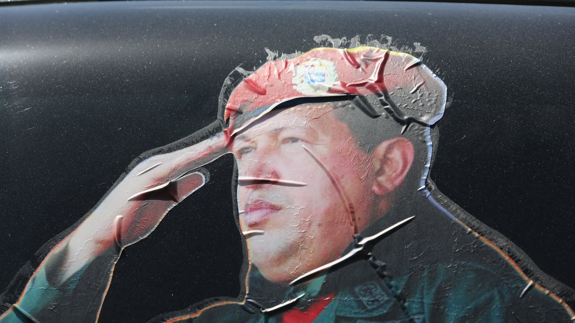 CARACAS, VENEZUELA - MARCH 04:  A sticker on a car window honors former Venezuelan president Hugo Chavez near the military barracks where Chavez is entombed on March 4, 2014 in Caracas, Venezuela. Workers made last minute preparations for Wednesday's ceremony marking the first anniversary of Chavez' death on March 5, 2013. The anniversary has been marred by three weeks protests against the government of Chavez' chosen successor Nicolas Maduro.  (Photo by John Moore/Getty Images)