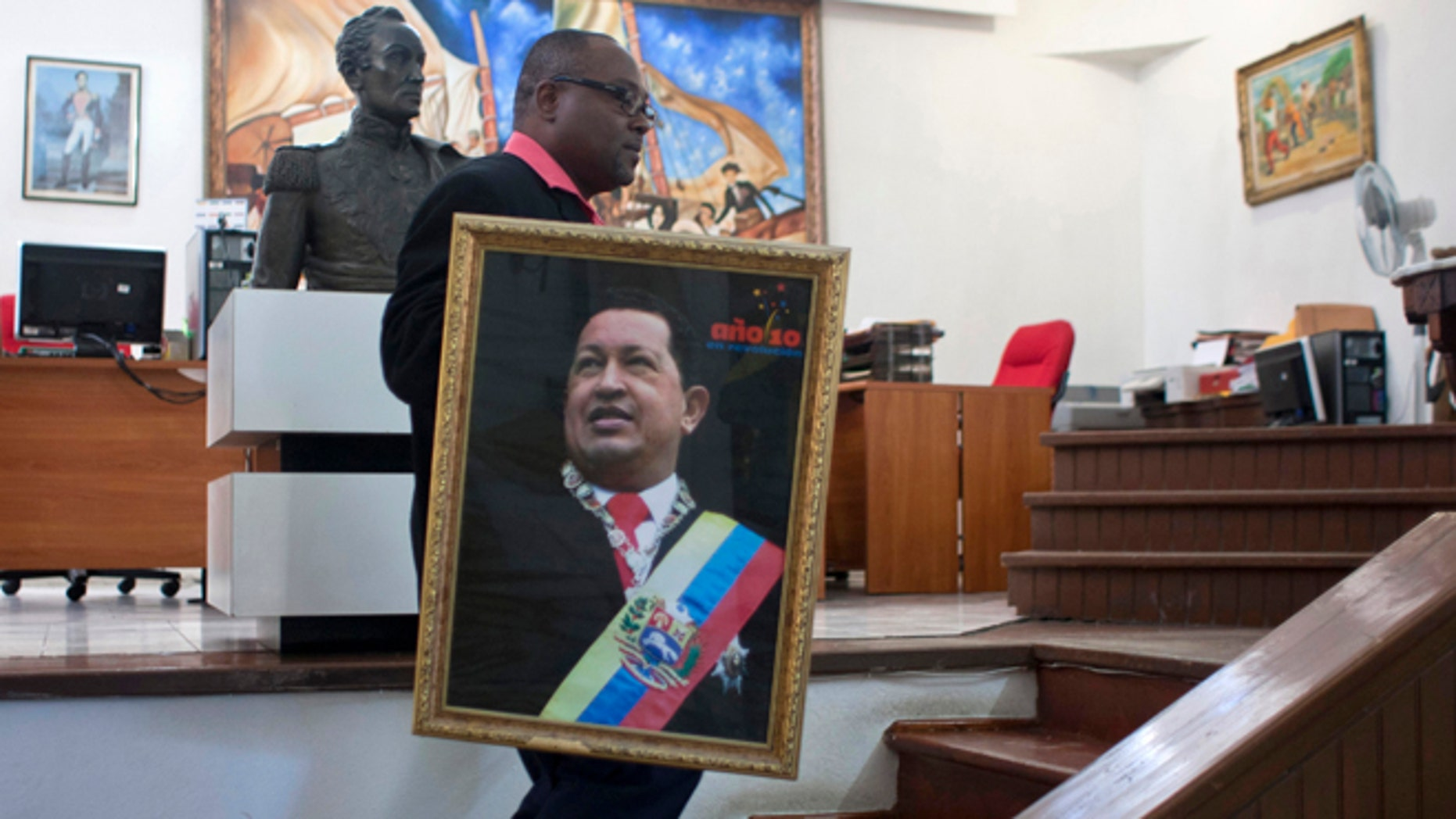Dec. 21, 2012: Pierre Denis, who works at Venezuela's embassy, carries an image of Venezuela's President Hugo Chavez after holding a Mass to pray for Chavez's health in Petion-Ville, Haiti.