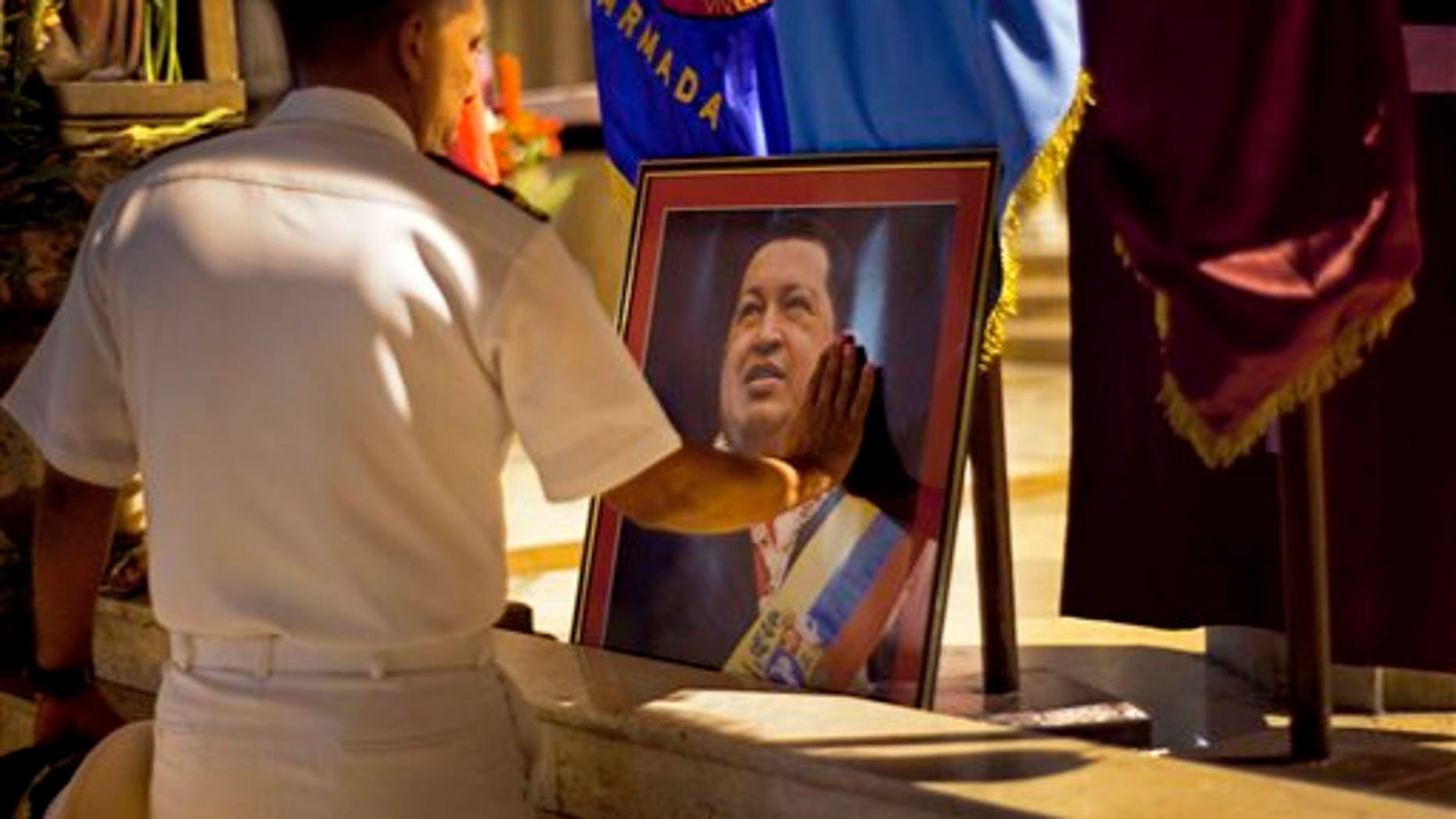 A member of Venezuela's navy touches an image of President Hugo Chavez after a mass in support of him in Havana, Cuba.