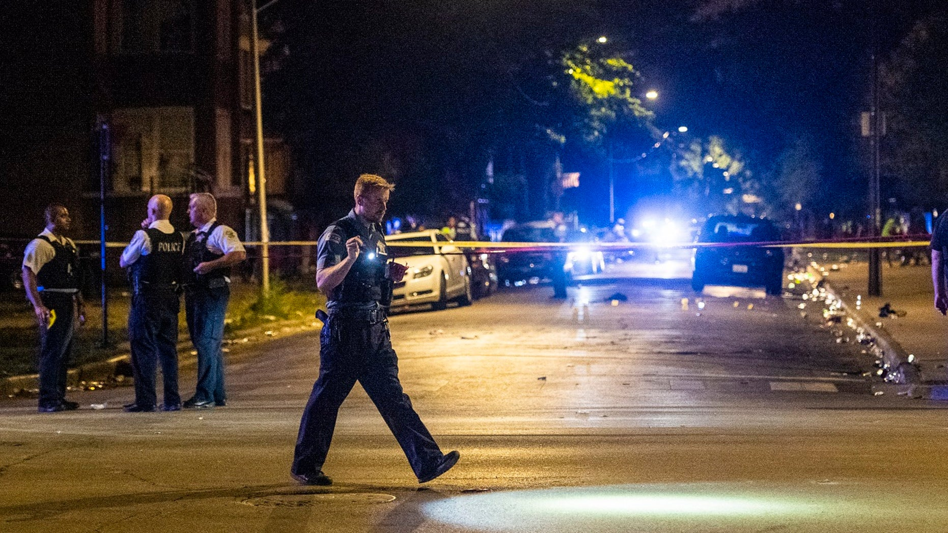 police investigate the scene where multiple people were shot in Chicago over the weekend.