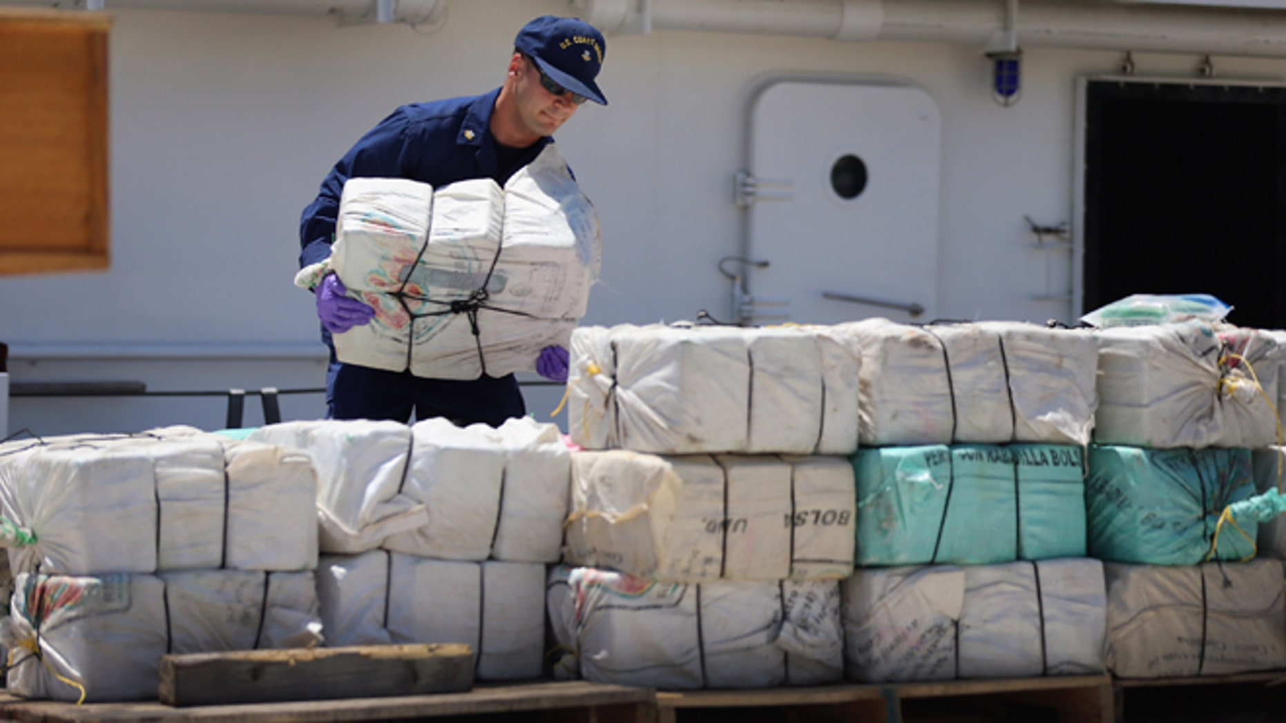 MIAMI, FL - APRIL 26:  A crew member from the Coast Guard Cutter Bernard C. Webber piles up some of the 2,200 pounds of cocaine after it was seized during Operation Martillo, worth an estimated $27 million on April 26, 2013 in Miami, Florida. The cocaine was found while the crew was conducting a law enforcement patrol, where they located a 68-foot fishing vessel in the western Caribbean Sea, April 18, 2013. The crew of the Cutter Gallatin boarded the vessel, located 2,200 pounds of cocaine, and detained three suspected smugglers.  (Photo by Joe Raedle/Getty Images)
