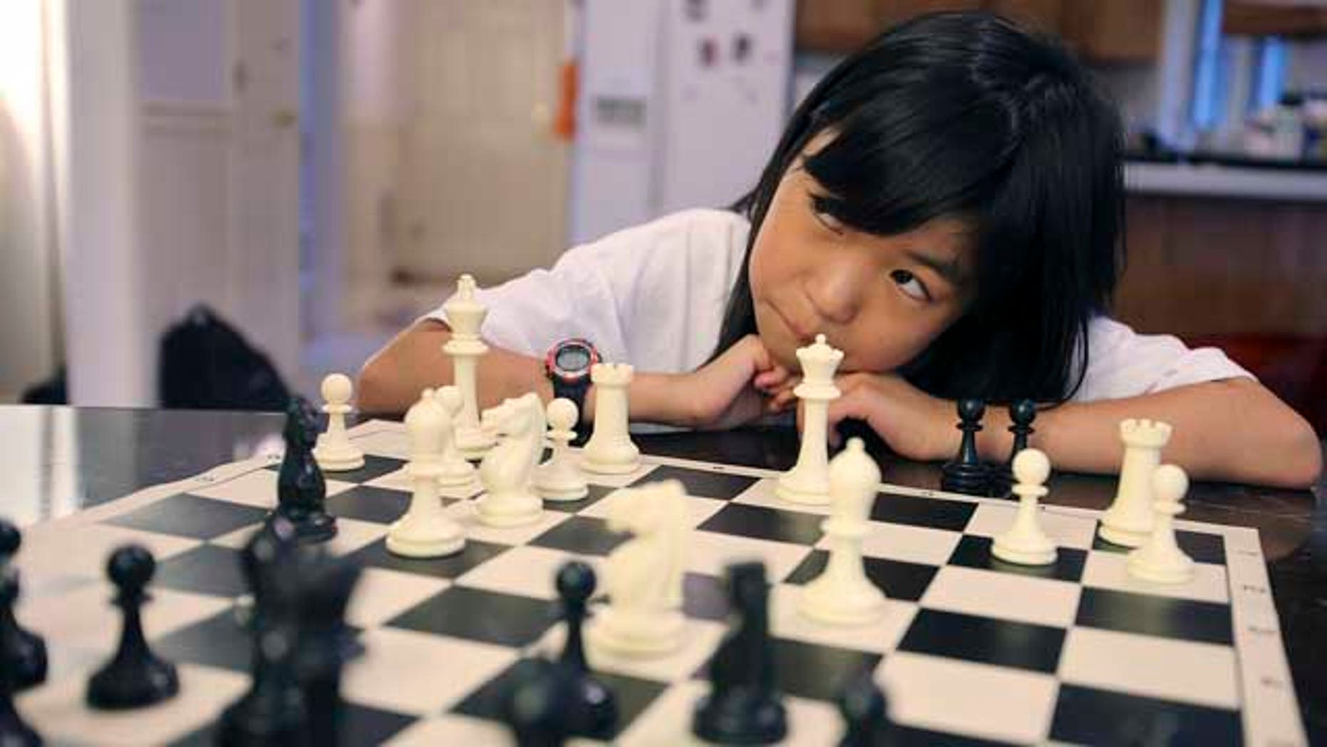 July 9, 2013: Carissa Yip, 9, waits for her father Percy Yip to make a move during a chess match at their home in Chelmsford, Mass.