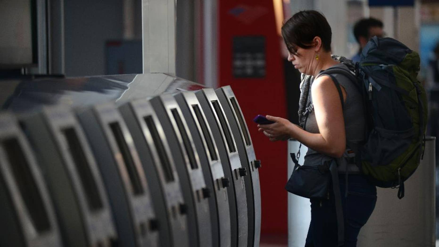 Breanne Eging checks on her flight to Greenville, South Carolina at O'Hare International Airport in Chicago, Friday, Sept. 26, 2014. All flights in and out of Chicago's two airports were halted Friday after a fire at a suburban air traffic control facility sent delays and cancellations rippling through the U.S. air travel network. Authorities said the blaze was intentionally set by a contract employee of the Federal Aviation Administration and had no ties to terrorism.   (AP Photo/Paul Beaty)