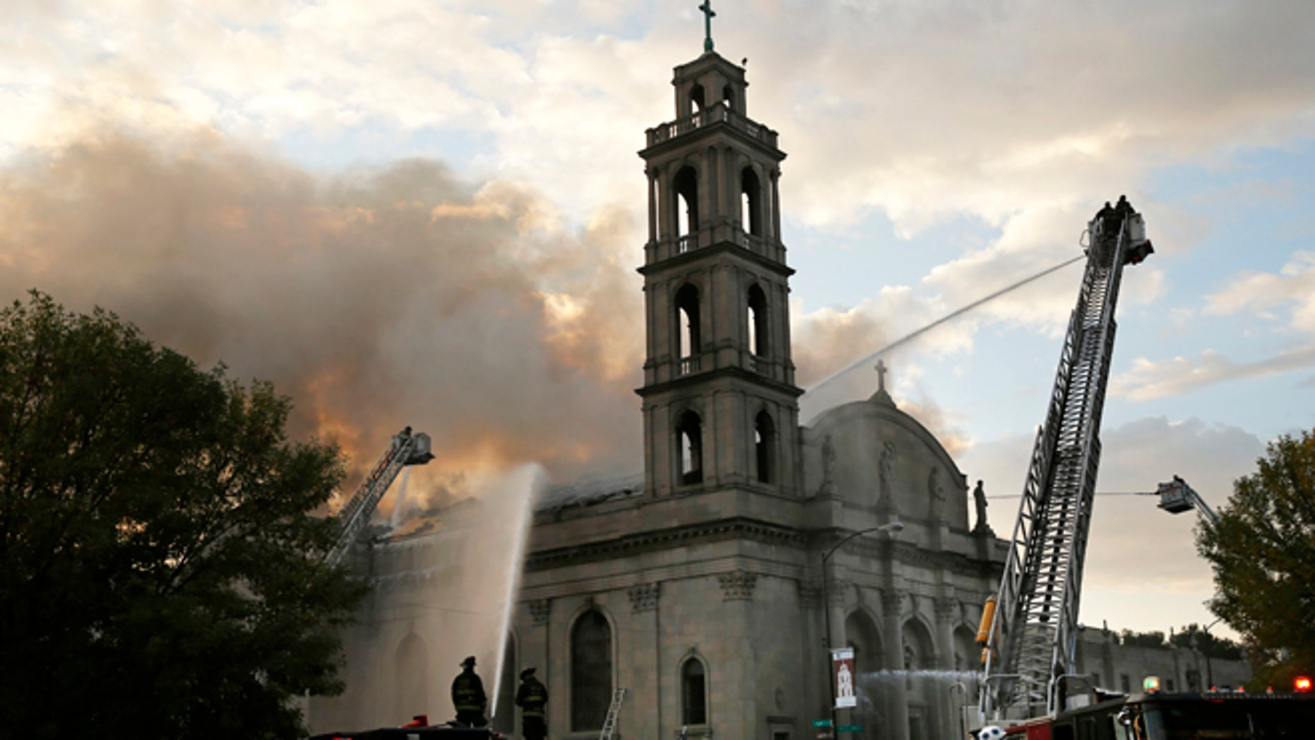 Chicago firefighters work at the scene of an extra-alarm fire at Shrine of Christ the King Church.