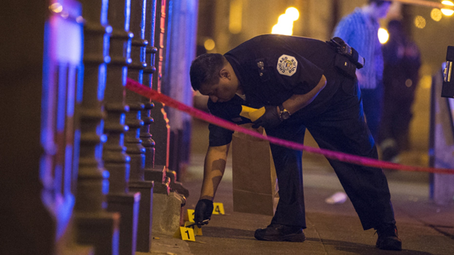July 5, 2015: A Chicago police officer collects evidence at a crime scene where a man was shot in the city.