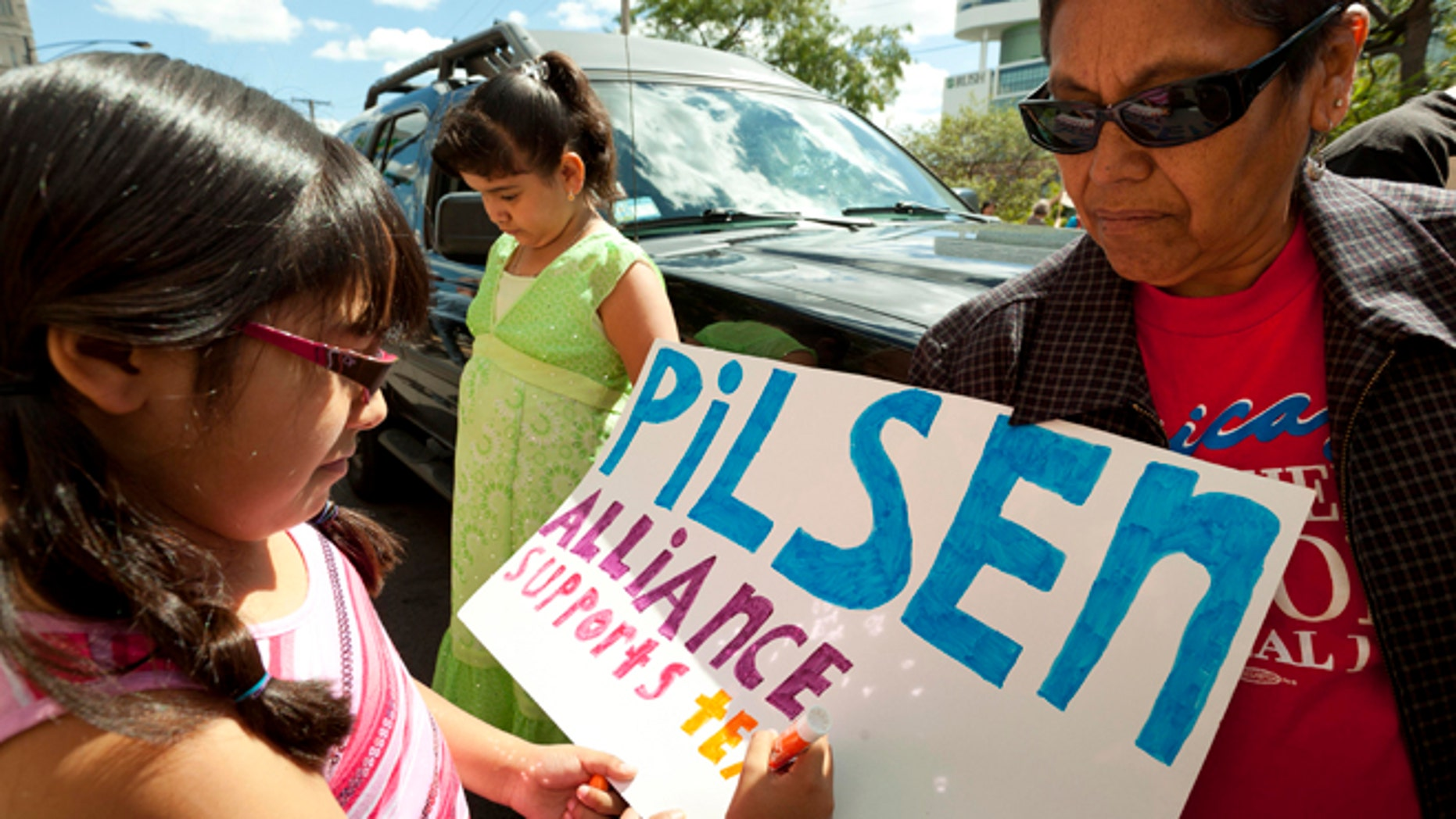 Sep. 8: Eight-year-old TaliSol Medina, left, a third-grader from Galileo School, puts the finishing touches on a pro-teachers poster for the Pilsen Alliance community group in front of the Chicago Teachers Union strike headquarters on Saturday in Chicago. AP Photo/Sitthixay Ditthavong)