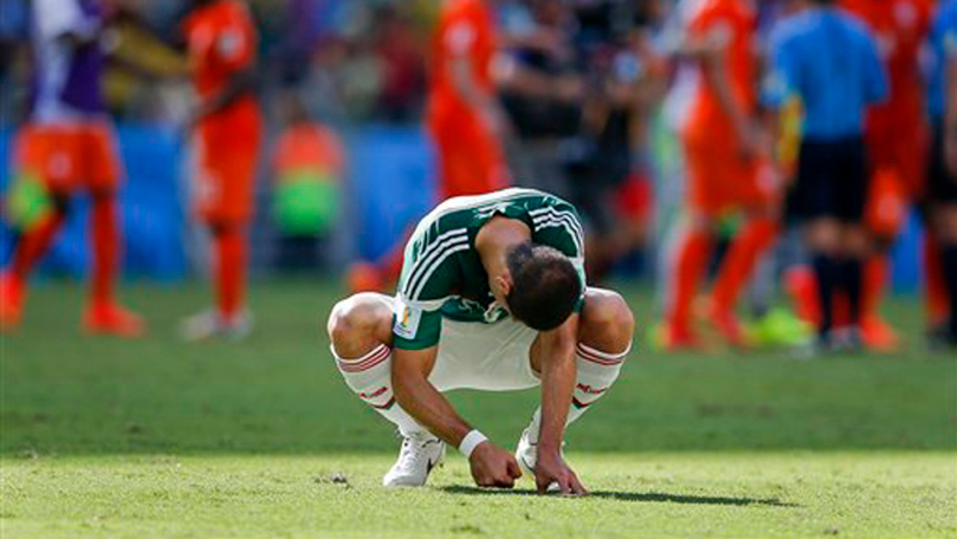 Mexico's Javier Hernandez punches the ground after the Netherlands defeated Mexico 2-1 to advance to the quarterfinals during the World Cup round of 16 soccer match between the Netherlands and Mexico at the Arena Castelao in Fortaleza, Brazil, Sunday, June 29, 2014. (AP Photo/Eduardo Verdugo)