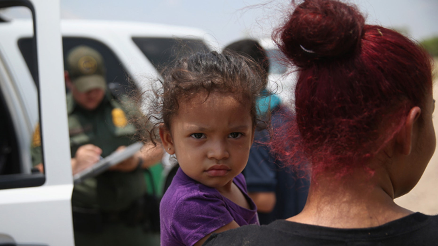 A mother and child, 3, from El Salvador await transport to a processing center for undocumented immigrants after they crossed the Rio Grande into the United States on July 24, 2014 in Mission, Texas. (Photo by John Moore/Getty Images)