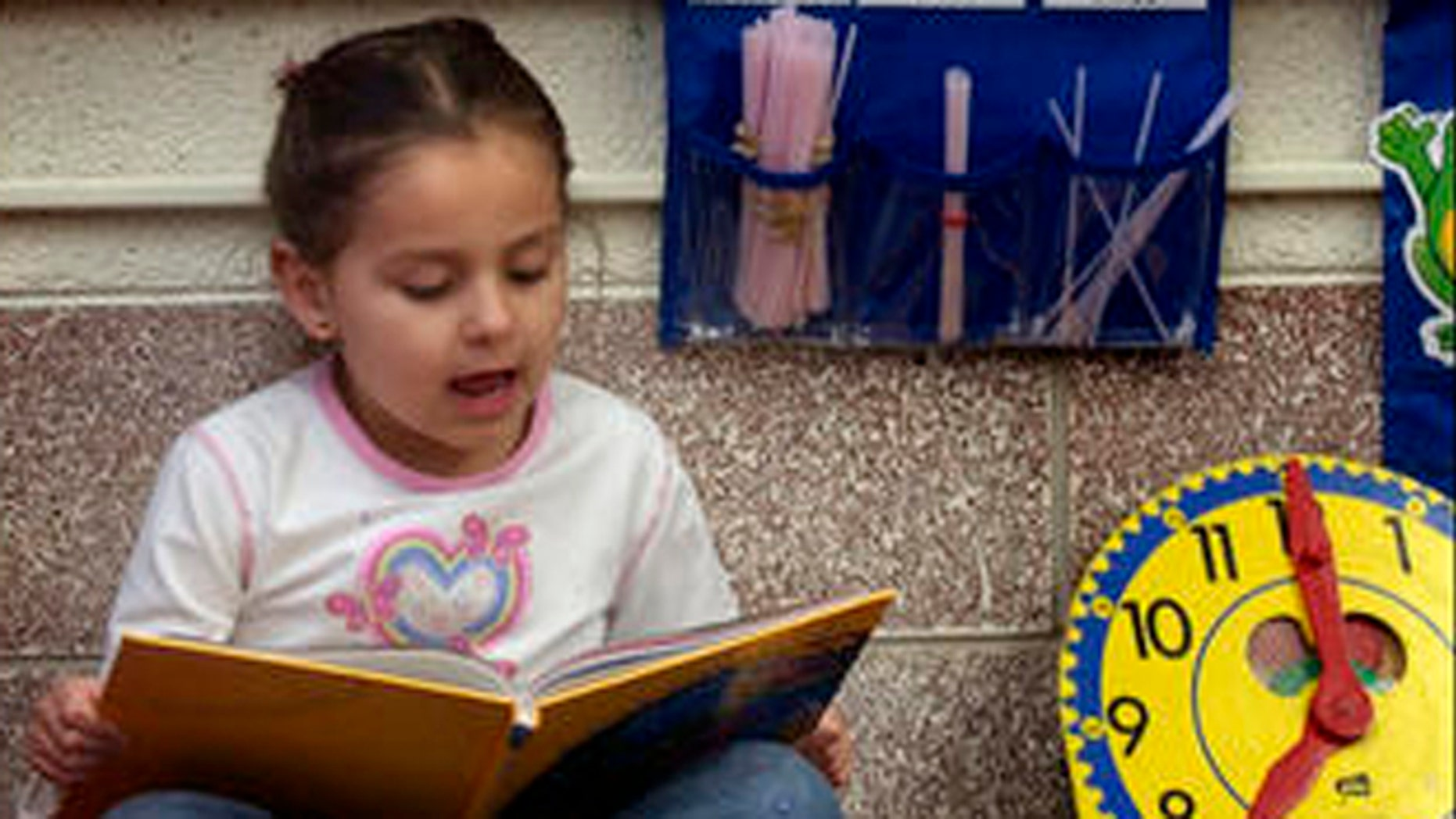 Kasandra Herrera, 6, reads a book in Spanish in Bianca Alvarez's dual language first grade classroom at Northwest Elementary School in Dodge City, Kan. Feb. 22, 2005. (AP Photo/Charlie Riedel)