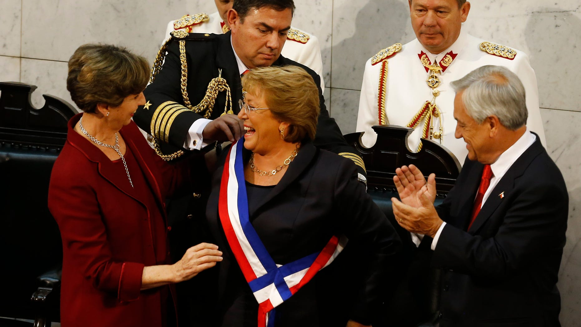 Bachelet receives the presidential sash from Senate President Isabel Allende, Tuesday, March 11, 2014.