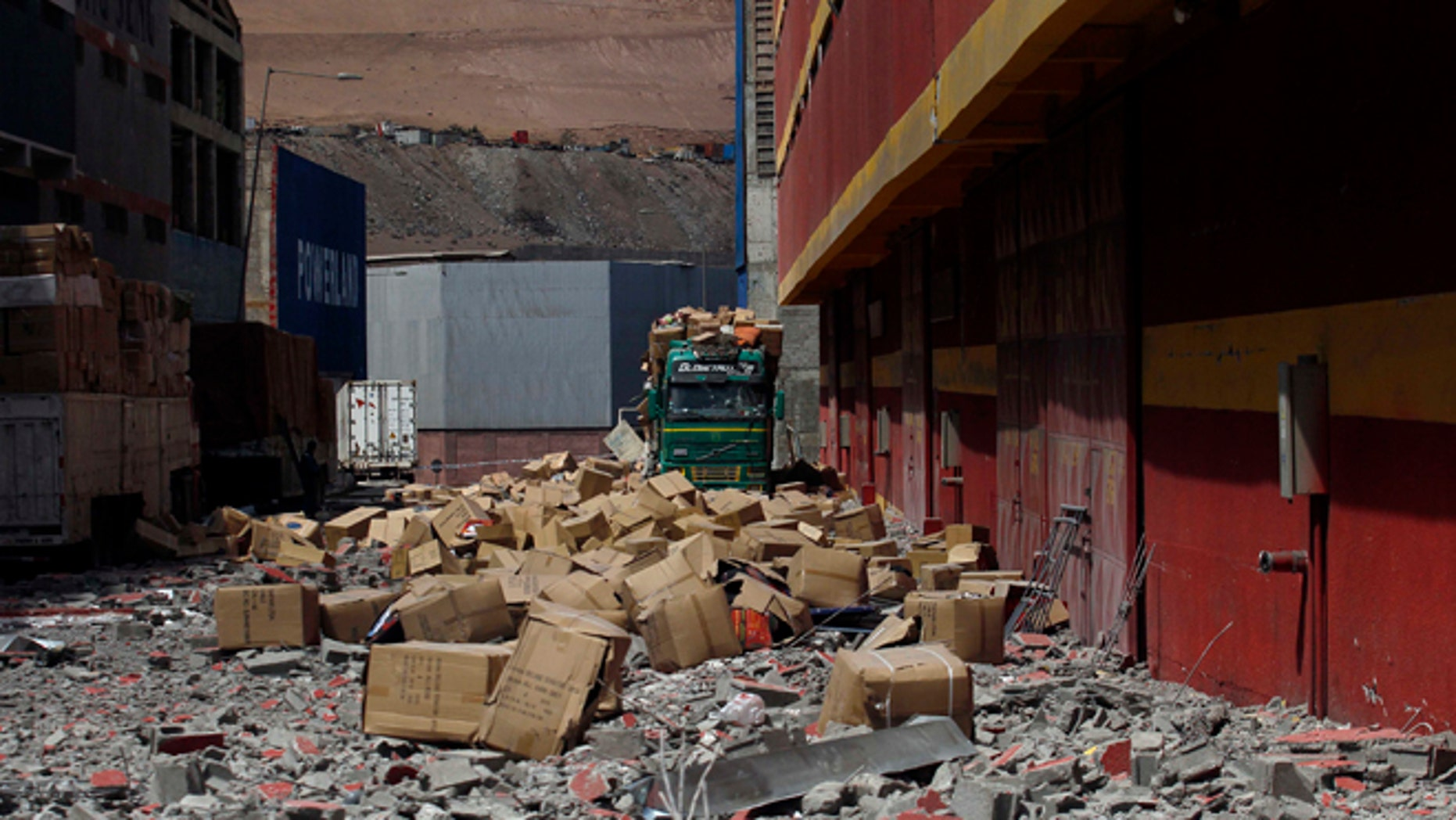 A truck remains covered by debris and boxes of fallen merchandise that fell from the earthquake ravaged Duty Free Zone of Iquique, in Iquique, Chile, Friday, April 4, 2014. Following a magnitude-8.2 earthquake early in the week, soldiers have kept a close watch on supermarkets and gas stations to prevent looting as many people continued to line up on Friday for gasoline, water and food. The city remained largely peaceful and no new major damage or casualties were reported from the continuing aftershocks that have rattled the sleep-deprived citizens of Chile's north. (AP Photo/Luis Hidalgo)