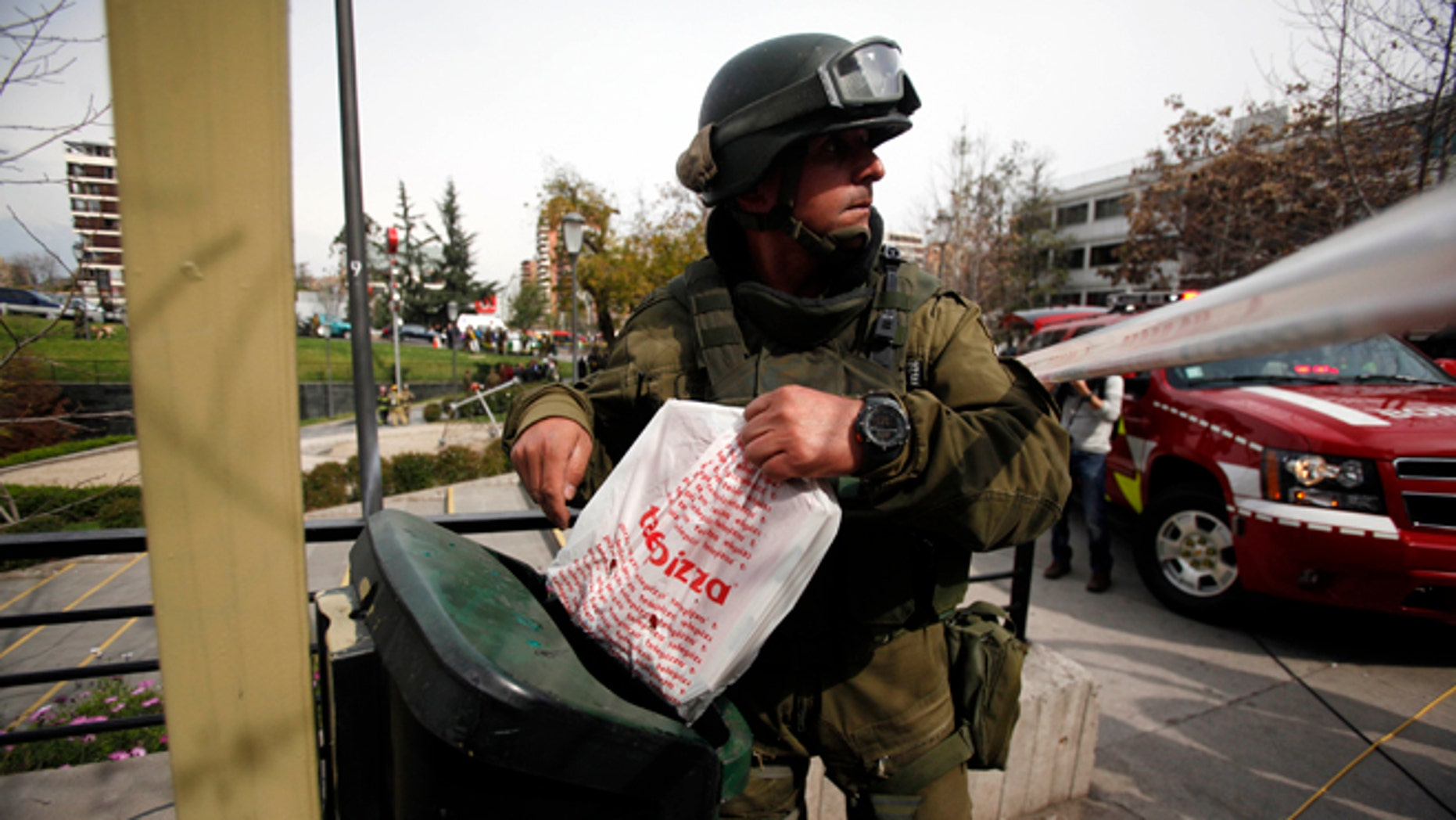 A police explosives expert inspects a garbage container near a blast site n Santiago, Chile, Monday Sept. 8, 2014.