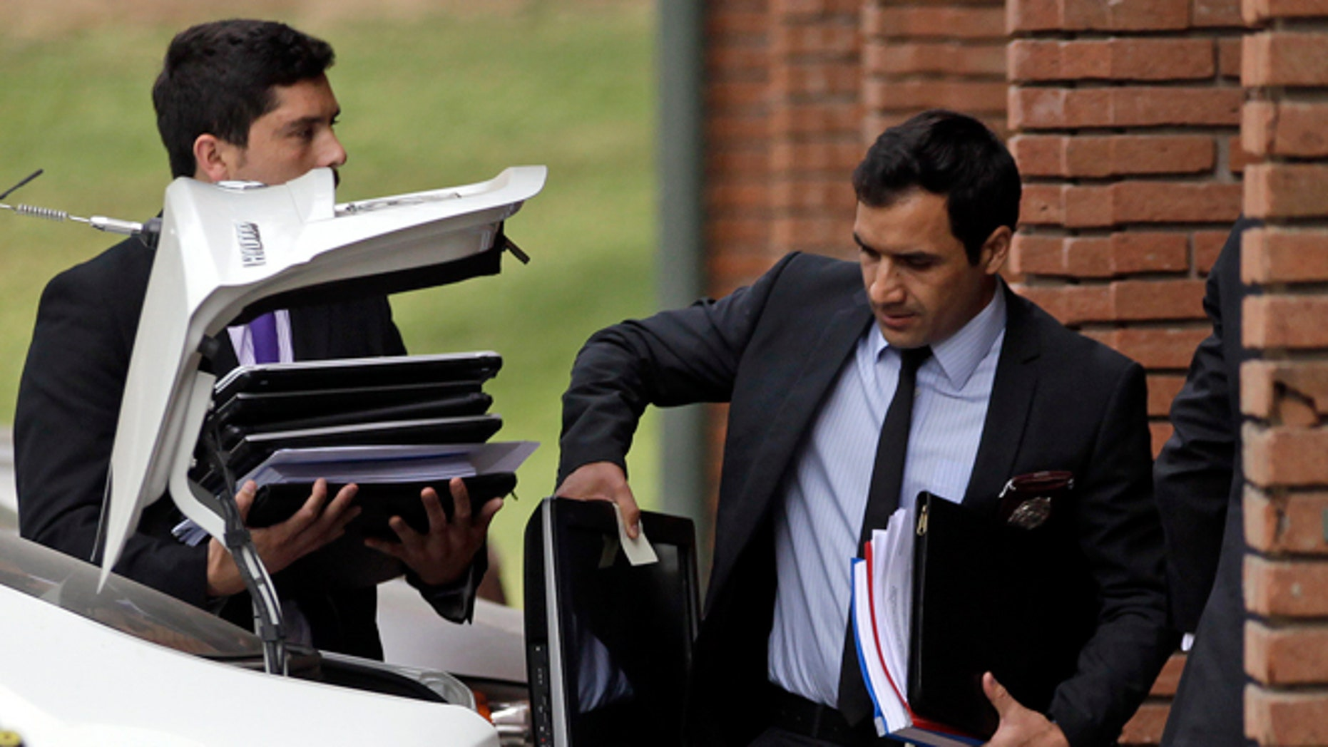 Police investigators carry documents and computers taken from the office of Chile's former president of the National Association of Professional Soccer, ANFP, Sergio Jadue, in Santiago, Chile, Thursday, Dec. 3, 2015.  U.S. prosecutors confirmed that Jadue had pleaded guilty to charges of racketeering conspiracy and wire fraud conspiracy, in the recent FIFA scandal. As part of their plea, Jadue agreed to forfeit all funds on deposit in his U.S. account. (AP Photo/Luis Hidalgo)