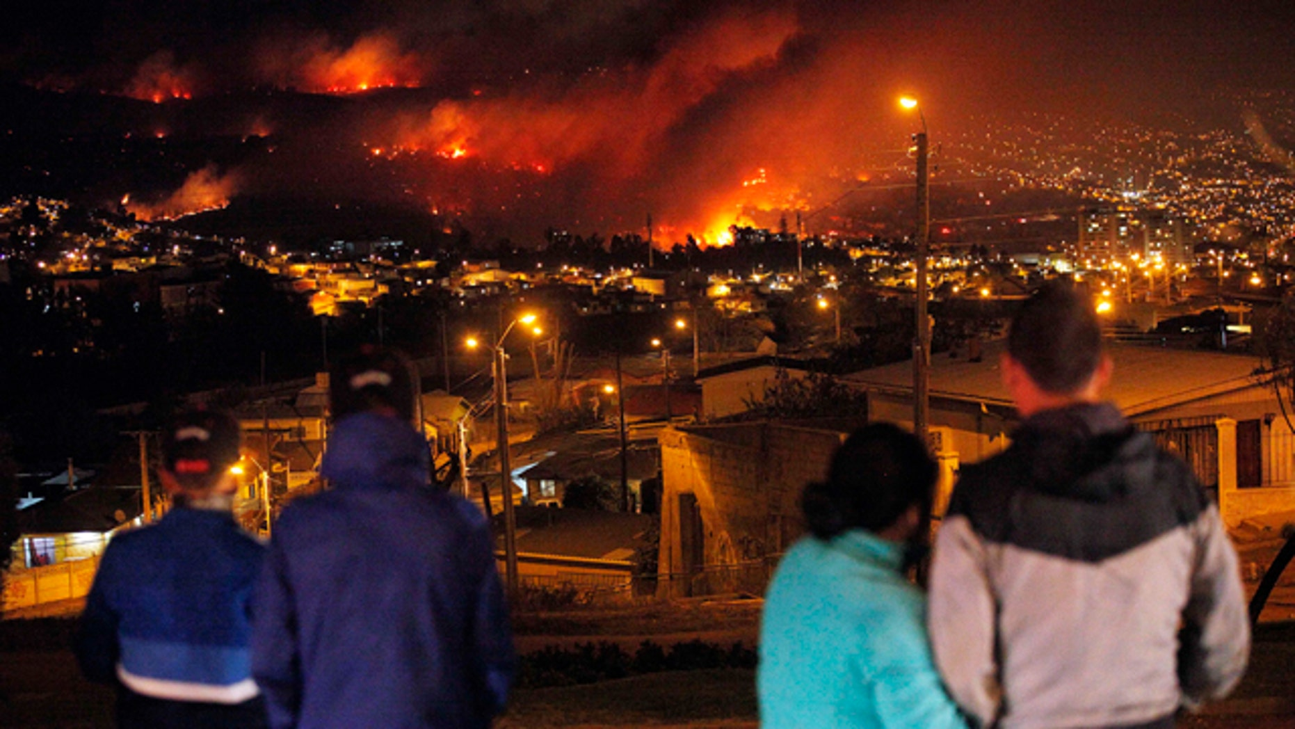 April 13, 2014: People watch as a forest fire rages towards urban areas in the city of Valparaiso, Chile. Authorities say the first fire has destroyed at least 500 homes and is forcing evacuations. ( AP Photo/ Luis Hidalgo)