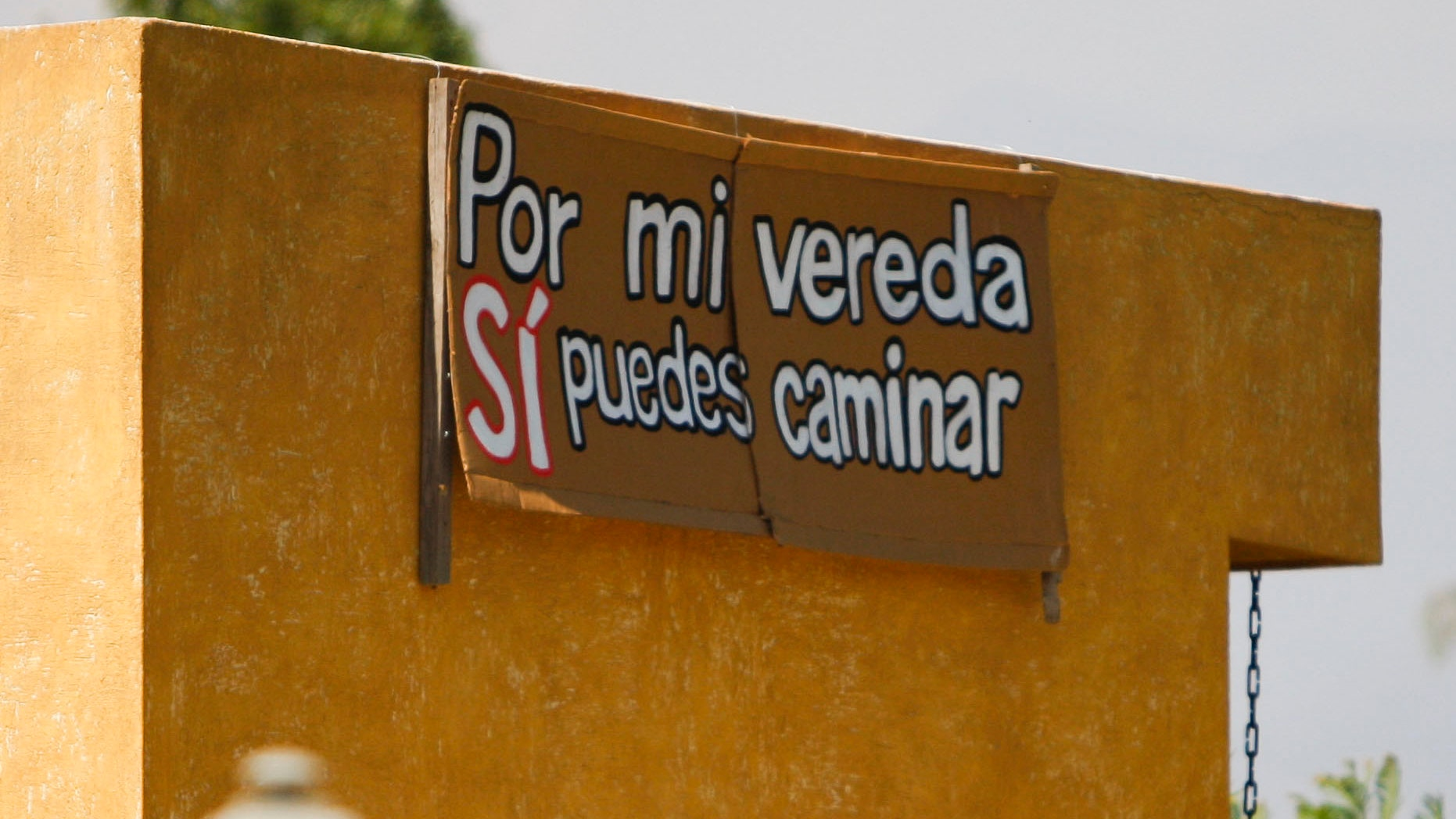 """A sign that reads in Spanish """"You can walk on my sidewalk""""; hangs on a wall of a house at the gated community of El Algarrobal II in Chicureo, Chile, Thursday Jan. 19, 2012. According to community rules, workers are forbidden to walk along it. The refusal of Felicita Pinto, a maid who works at the neighborhood, to get on a bus to carry her to her workplace, just a short walk away, has set off a soul-searching debate about class prejudice and exploitation in Chile and prompted a protest Saturday against discrimination. (AP Photo/Roberto Candia)"""