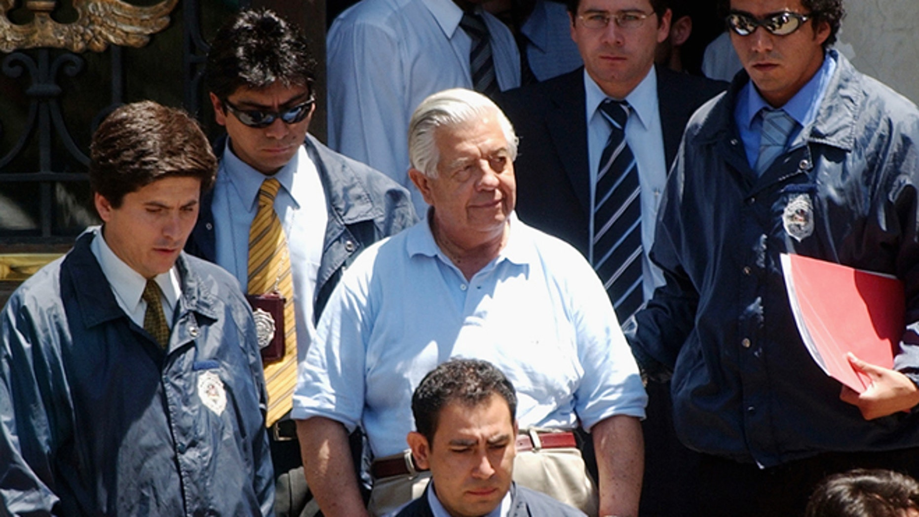FILE.- In this Jan. 28, 2005 file photo retired Gen. Manuel Contreras, center,  is escorted by police officers in Santiago, Chile.   According to Chile's government, Contreras, the former chief of Chile's spy agency responsible for the kidnapping and torture of thousands during the Pinochet military dictatorship died Friday in Santiago's military hospital. He was 86.(AP Photo, File)