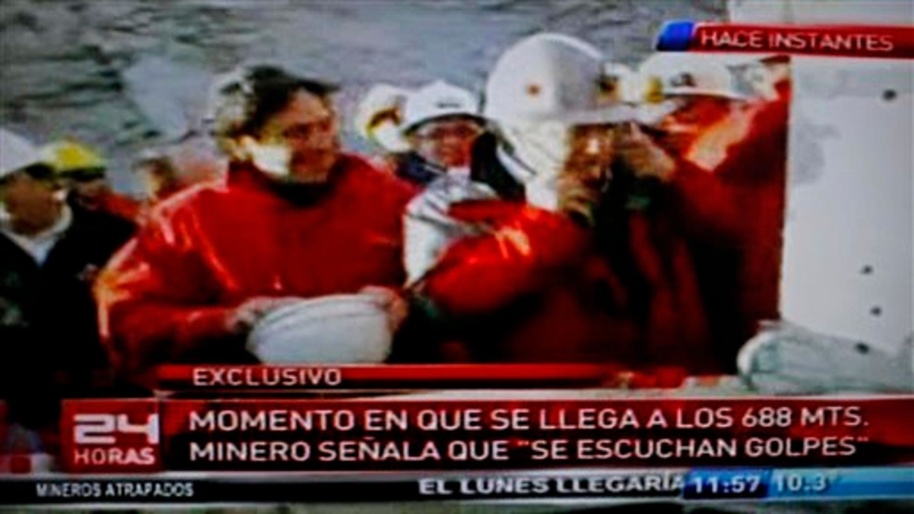 """In this frame grab from TV channel 24 Horas, Chile's Mining Minister Laurence Golborne, left, smiles as an unidentified official listens with a medical oscilloscope to unknown sounds coming from the area of a collapsed mine where about 33 miners have been trapped for 17 days in Copiapo, Chile, Sunday, Aug. 22, 2010.  The miners have been trapped below the surface since the main access collapsed on Aug. 5 due to tons of falling rock.  The text at bottom reads in Spanish """"Moment that it (a drill) reaches 688 meters. Miner indicates that 'knocking is heard'."""" (AP Photo)"""