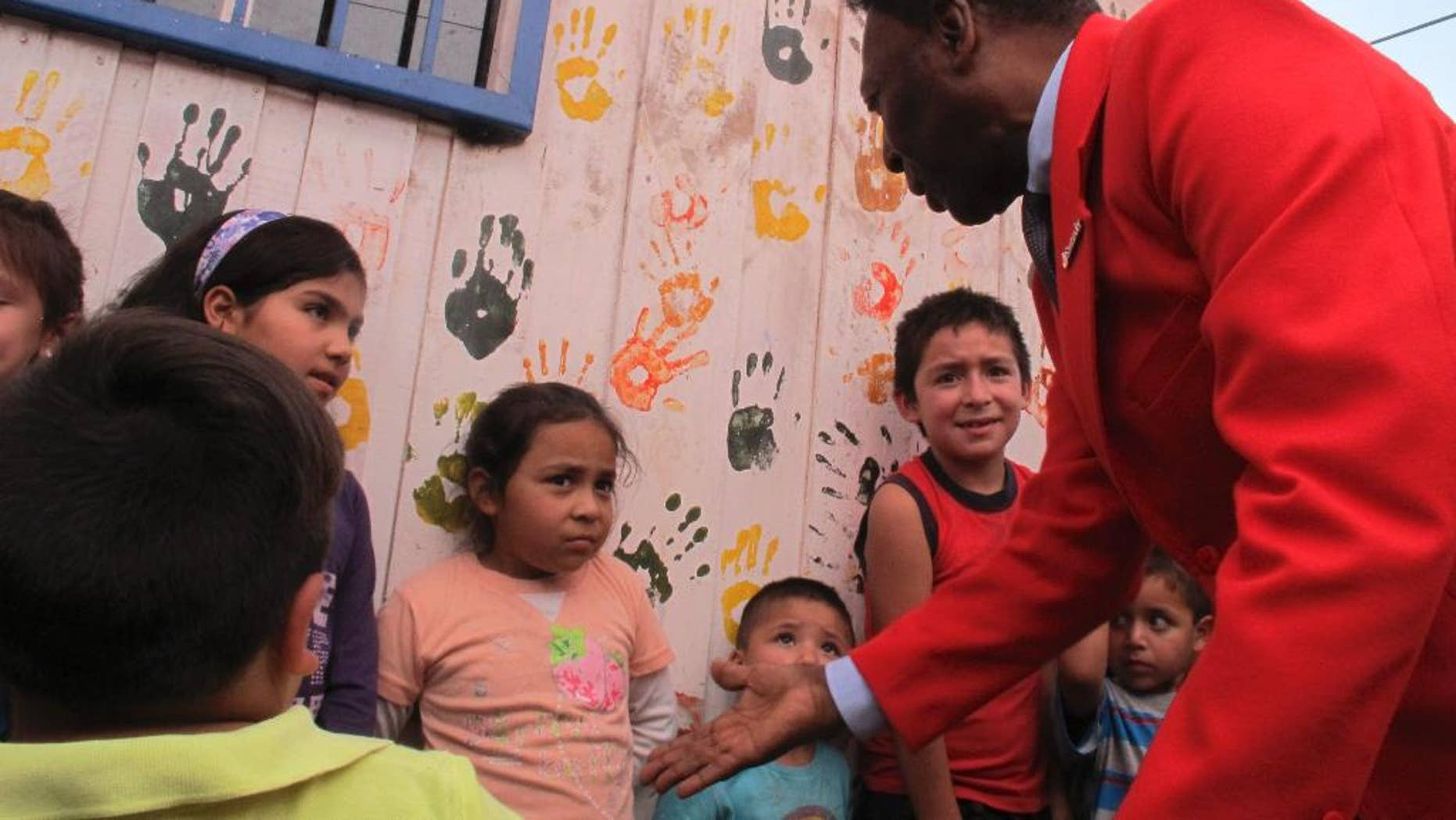 """Brazilian soccer legend Pele puts out his hand, while greeting children in a visit to a slum in Santiago, Chile, Thursday, April 9, 2015. The activity was organized Thursday by a local NGO and a bank, seeking to inspire Chilean children. Pele says he has """"happily recovered"""" from a recent health scare. (AP Photo/Luis Andres Henao)"""