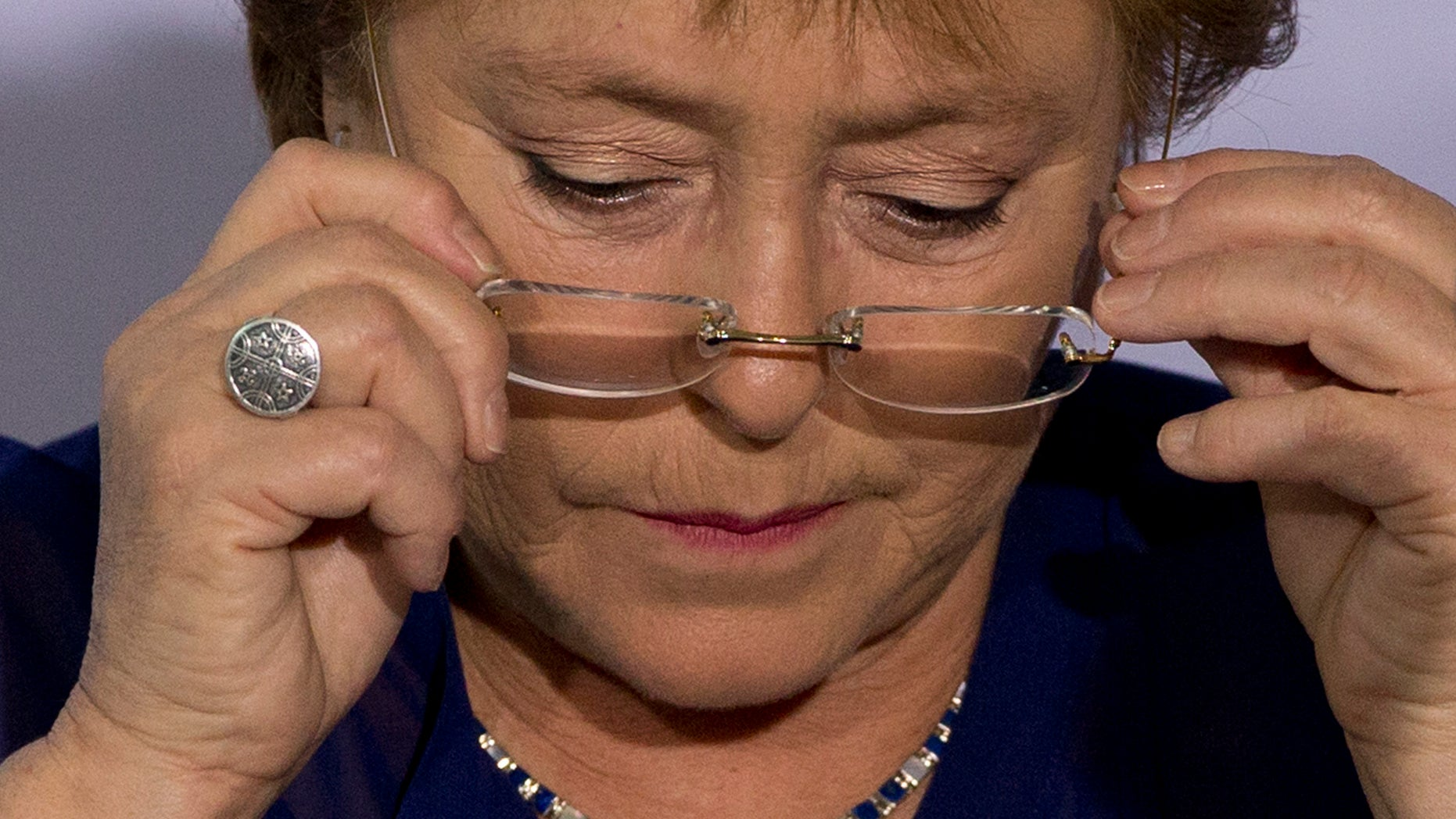 FILE - In this Dec. 9, 2014, file photo, Chile's President Michelle Bachelet puts on her glasses during an event to announce a new economic report on Latin America at the 2014 Iberoamerican Summit in Veracruz, Mexico. President Bachelet came under fire on Wednesday Feb. 11, 2015, over complaints her family got privileged access to a bank loan for a land deal. Chile's Que Pasa magazine reported that a company half-owned by Bachelet's daughter-in-law, Natalia Compagnon, received a $10 million loan from Banco de Chile. (AP Photo/Rebecca Blackwell, File)