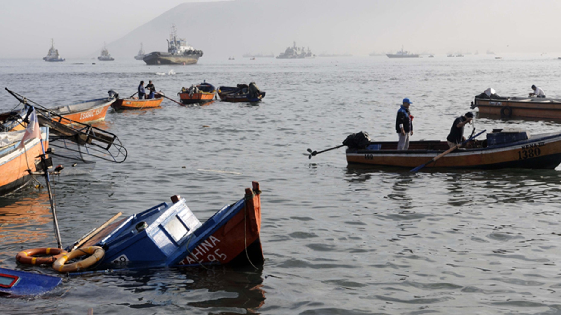 Fishing boats lie damaged by a small tsunami, in the northern town of Iquique, Chile, after magnitude 8.2 earthqauke struck the northen coast of Chile, Wednesday, April 2, 2014. Authorities lifted tsunami warnings for Chiles long coastline early Wednesday. Six people were crushed to death or suffered fatal heart attacks, a remarkably low toll for such a powerful shift in the Earths crust. (AP Photo/Cristian Viveros) NO PUBLICAR EN CHILE