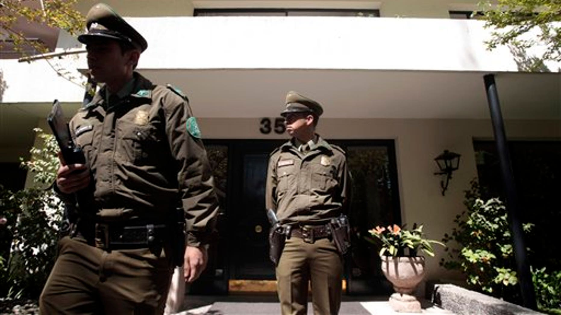 Policemen stand guard at the residence entrance of suicide victim, former Chilean Gen. Odlanier Mena, in Santiago, Chile, Saturday, Sept. 28, 2013. The 87-year-old retired general was serving time for human rights violations but was allowed weekend home visits. He committed suicide at his home, hours before he was to return to his prison cell. Mena was the first director of the National Information Center, the secret police force created by dictator Gen. Augusto Pinochet. (AP Photo/Luis Hidalgo)