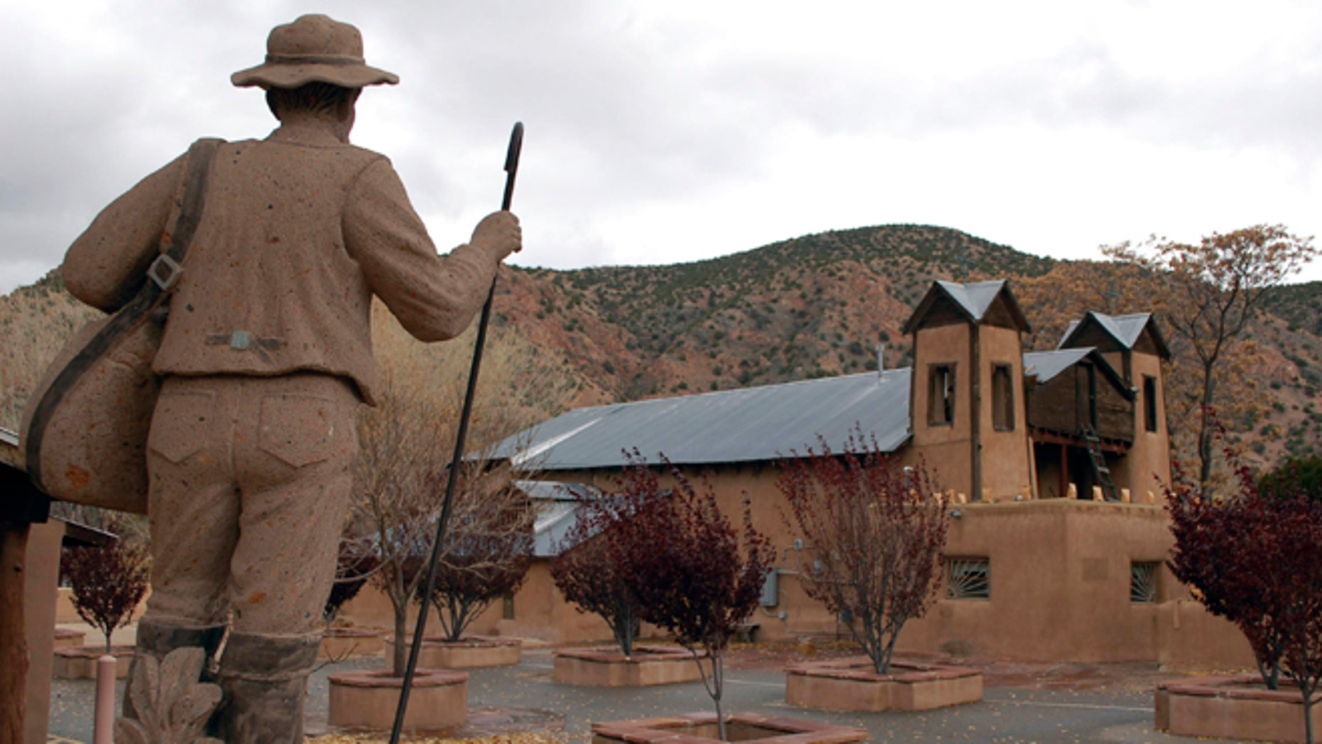 FILE- A Nov. 13, 2011, file photo shows El Santuario de Chimayo outside of Espanola, N.M.  The popular northern New Mexico Catholic shrine that attracts thousands each year is working to fight persistent vandals. A benefit concert fo by world-renowned cellist Michael Fitzpatrick is scheduled on July 19,2013 outside the Santuario. (AP Photo/Russell Contreras, File)