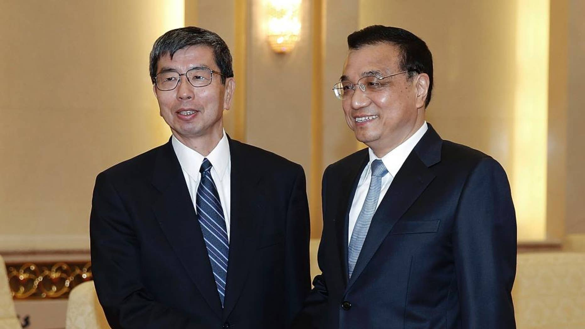 FILE - In this March 23, 2015 file photo, Asian Development Bank President Takehiko Nakao, left, poses with Chinese Premier Li Keqiang for a photo at the Great Hall of the People in Beijing. The president of the Asian Development Bank says a proposed Chinese-led regional bank is a potential partner instead of a rival and the ADB is talking with Beijing to share its experience. (AP Photo/Lintao Zhang, Pool, File)