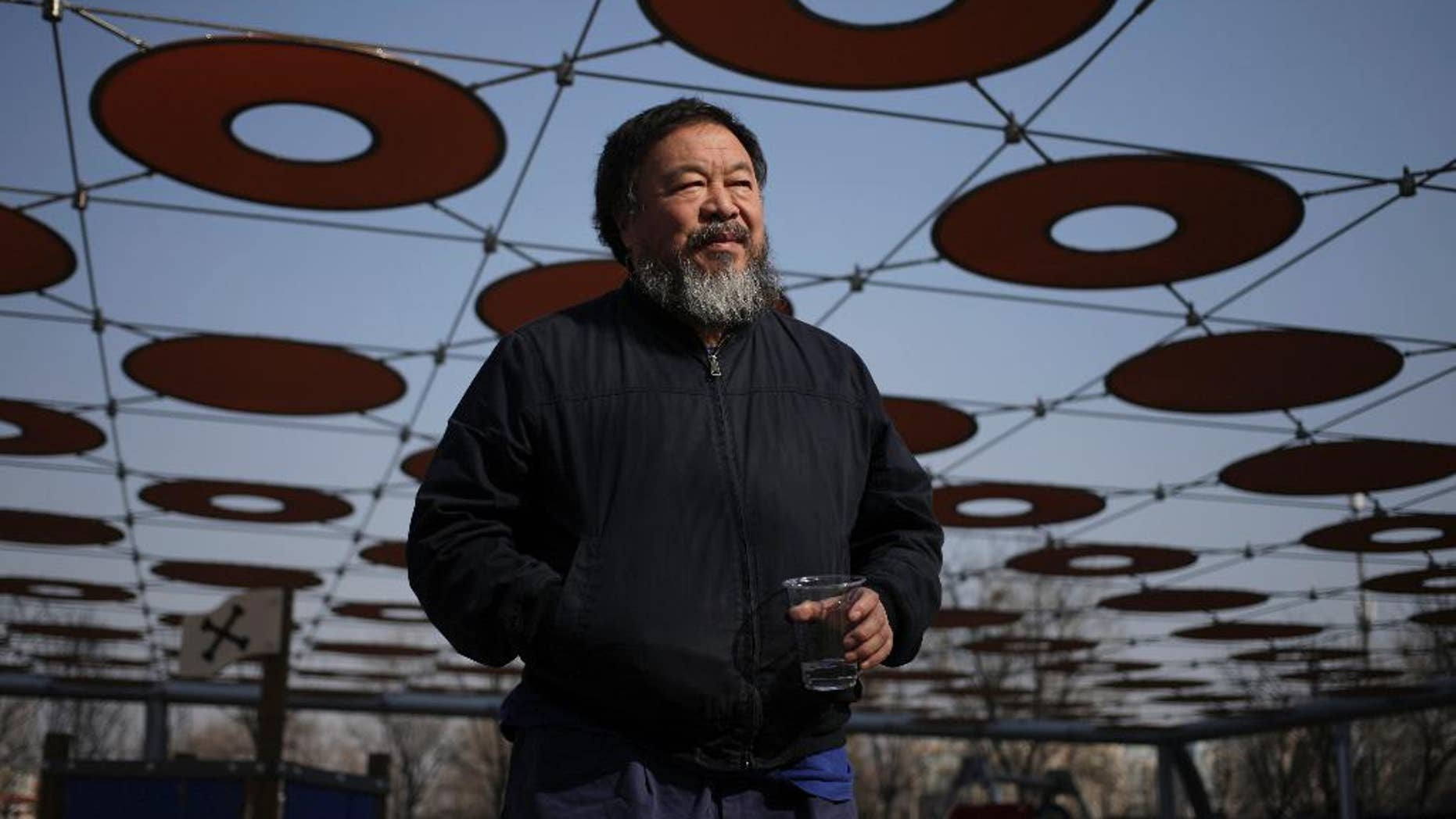 """FILE - In this March 24, 2015 file photo, Chinese dissident artist Ai Weiwei walks near a playground outside a shopping mall in Beijing. Ai has his passport back four years after it was confiscated by authorities. Ai on Wednesday, July 22, 2015, posted a photo of himself on Instagram holding a Chinese passport with the caption, """"Today, I got my passport."""" (AP Photo/Andy Wong, File)"""