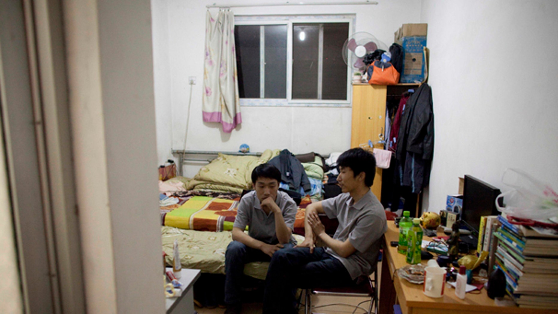 May 11: 24-year-old engineer graduates Liu Jun and Li Zhenyang rest in their rented room at Tang Jialing village where tens of hundreds of young educated Chinese crowd in shared rooms in Beijing, China. (AP)