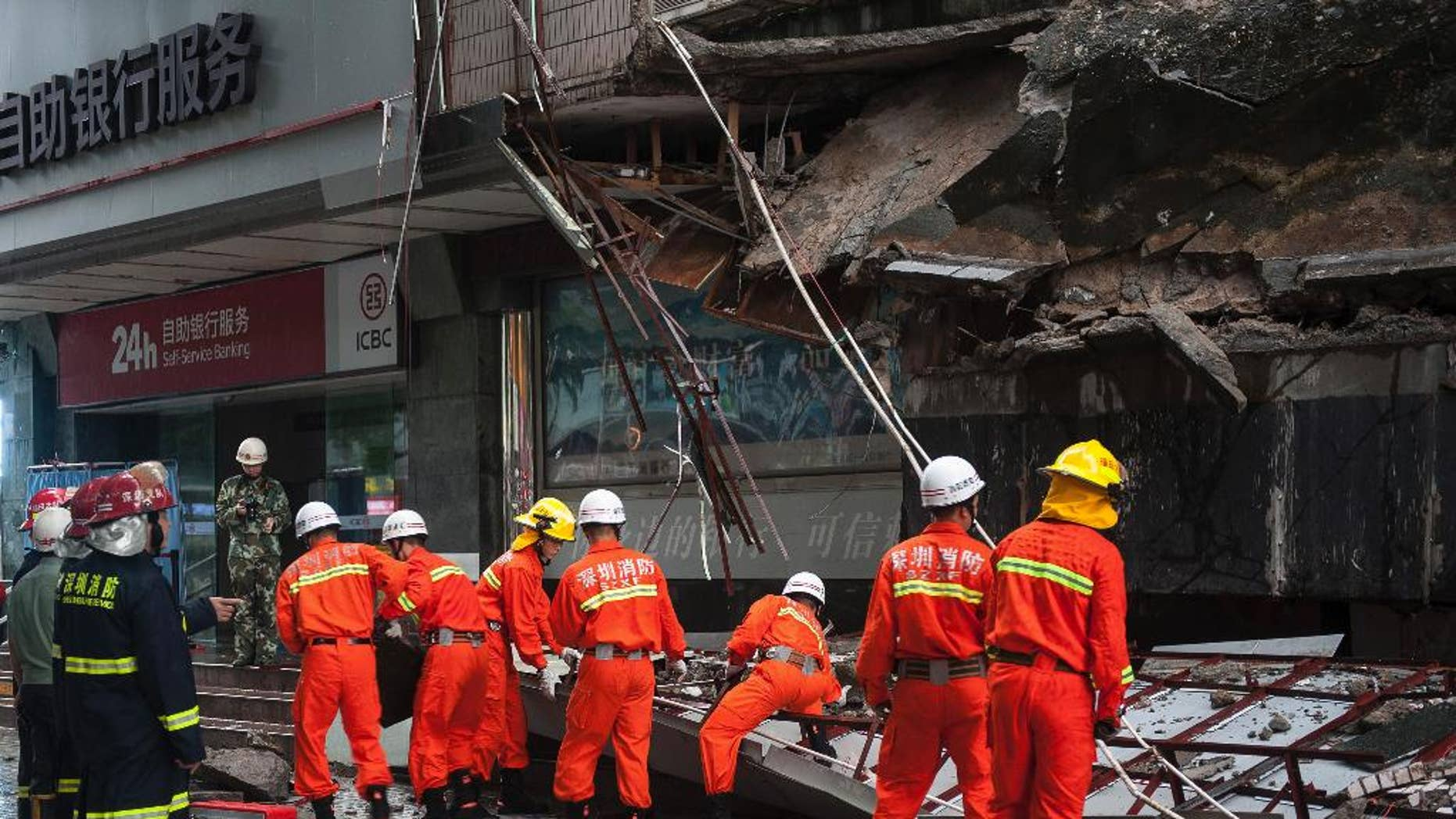 Rescuers try to remove a steal frame from a collapsed concrete roof which has killed and injured a number of people after they took shelter during heavy rains in Shenzhen in south China's Guangdong province Friday, July 18, 2014. A powerful typhoon hit the southern Chinese island of Hainan on Friday after killing tens people in the Philippines. (AP Photo) CHINA OUT