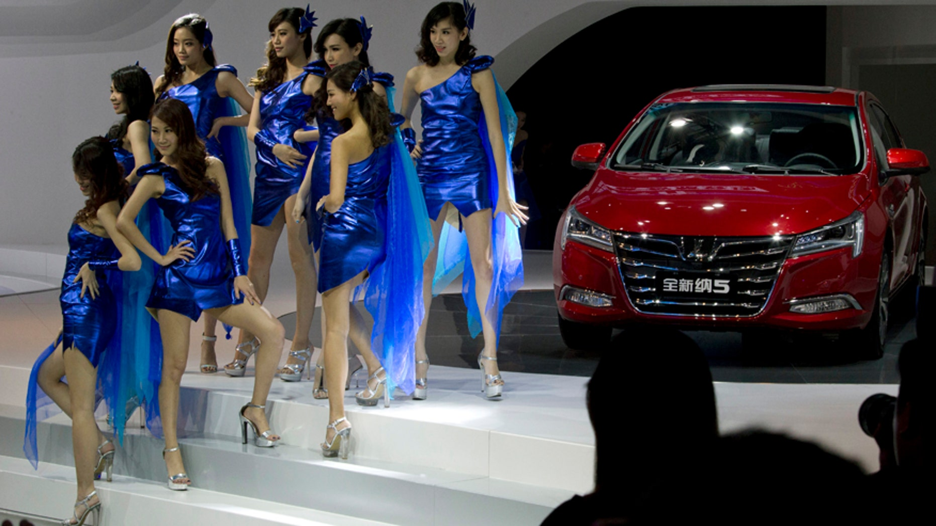 Taiwanese dancers introduce a new car from Luxgen, a joint venture between state-owned Dongfeng Motor Co. and Yukon, a Taiwanese partner in Shanghai, Monday, April 20, 2015. The Shanghai Auto Show banned female models and automakers responded with dancers and fresh-faced young women holding tablet computers. (AP Photo/Ng Han Guan)