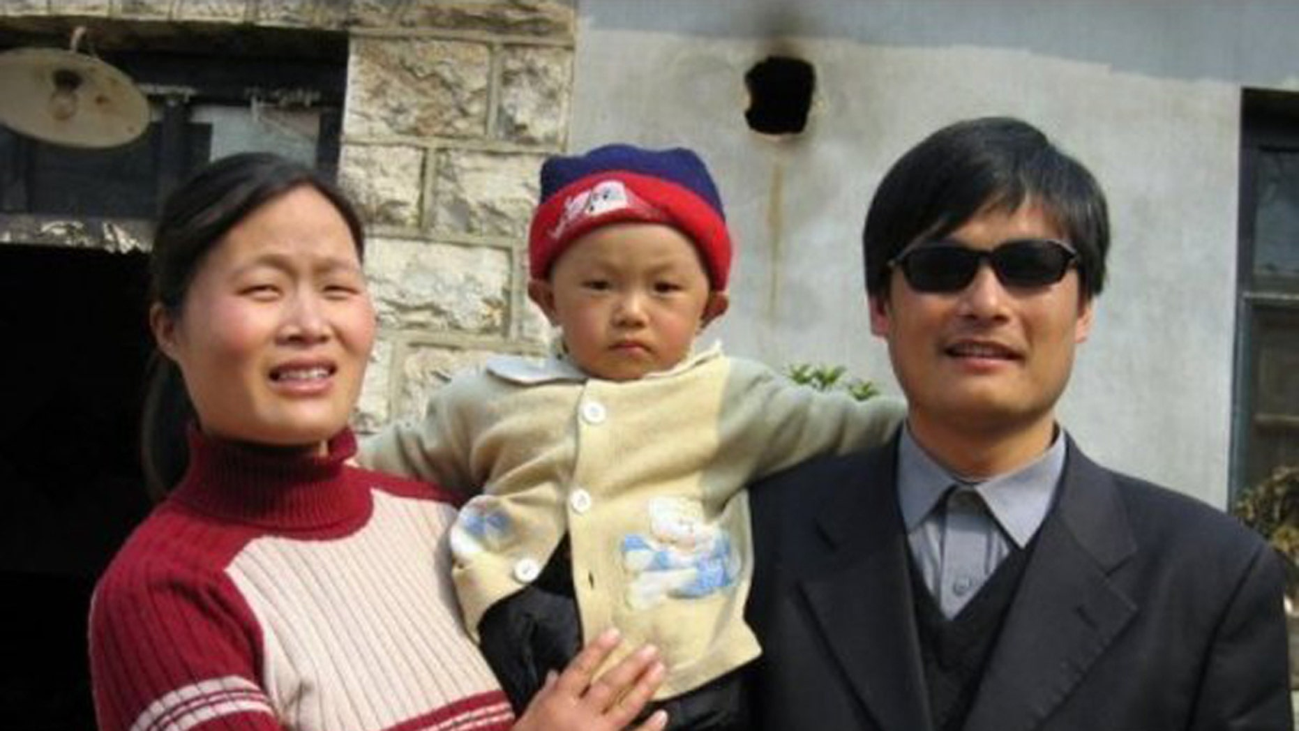 This undated photo provided by the China Aid Association shows blind Chinese legal activist Chen Guangchen, right, with his son, Chen Kerui, with his wife Yuan Weijing, left, in Shandong province, China.