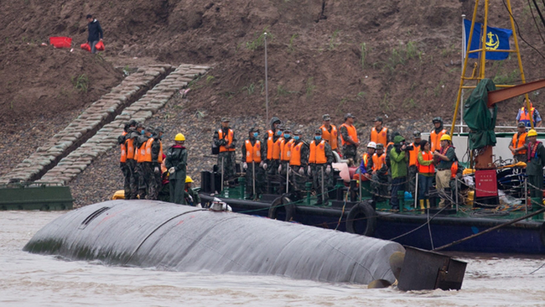 June 3, 2015: Rescue workers gather on the hull of a capsized cruise ship, center, on the Yangtze River in central China's Hubei province. (AP Photo/Andy Wong)