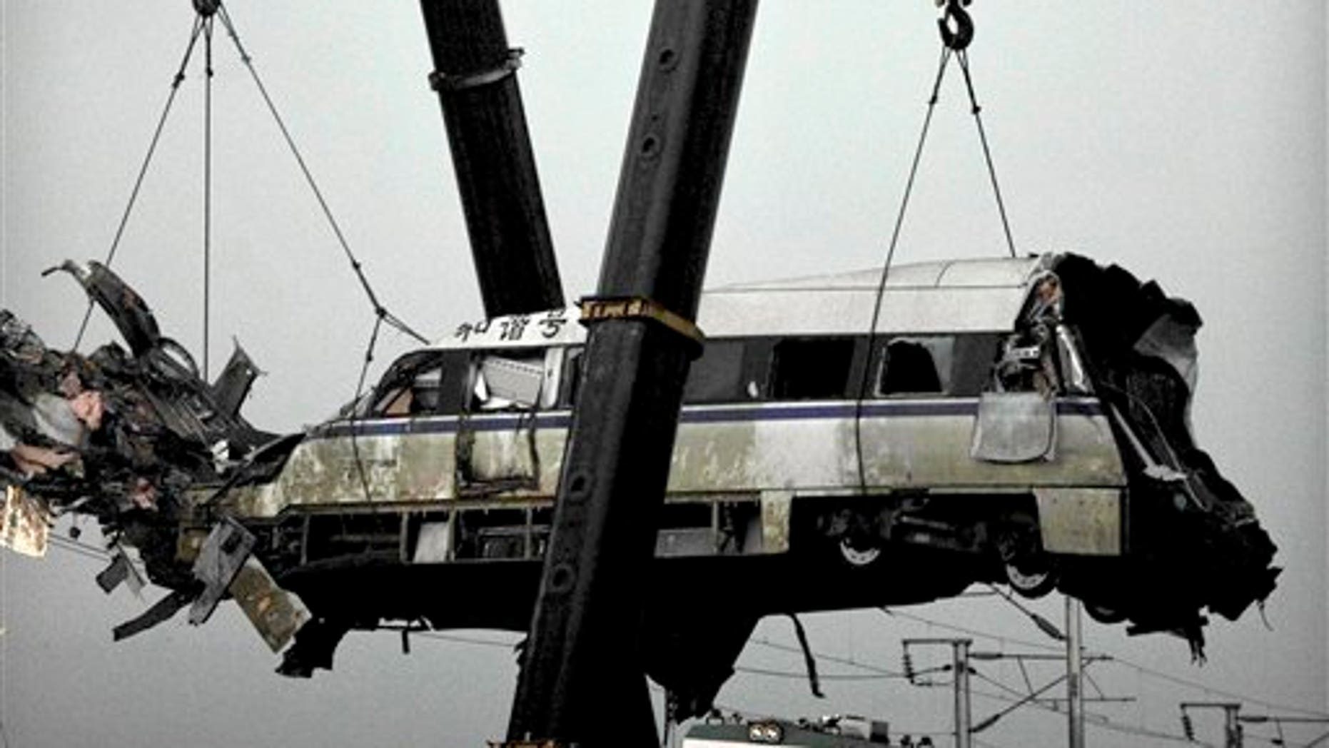 July 24, 2011: A wrecked passenger carriage is lifted off the bridge in Wenzhou in east China's Zhejiang province, after a train crash.